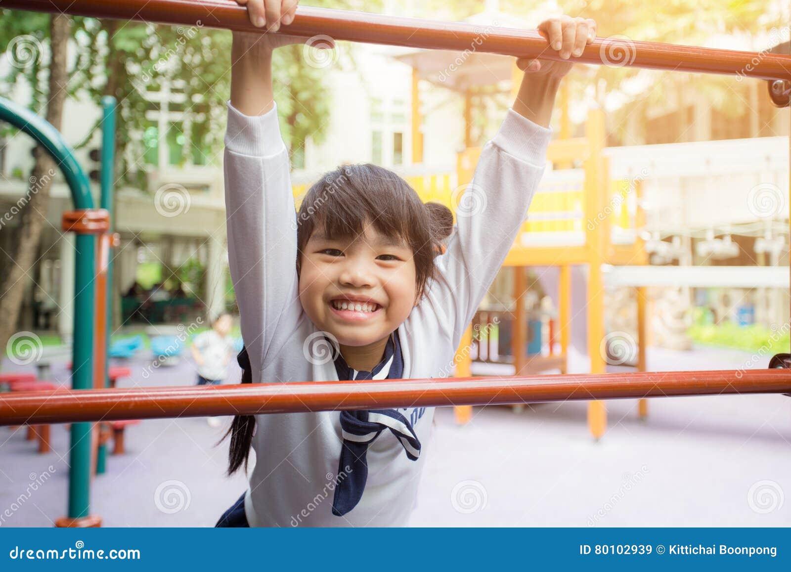Crianças de Ásia do retrato que sentem o campo de jogos das crianças felizes no parque público exterior para