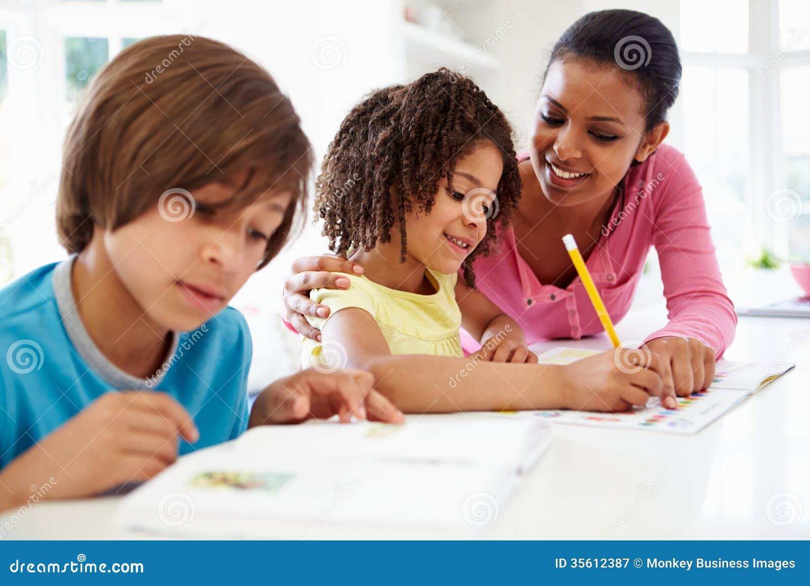 Crianças de ajuda da mãe com trabalhos de casa na cozinha