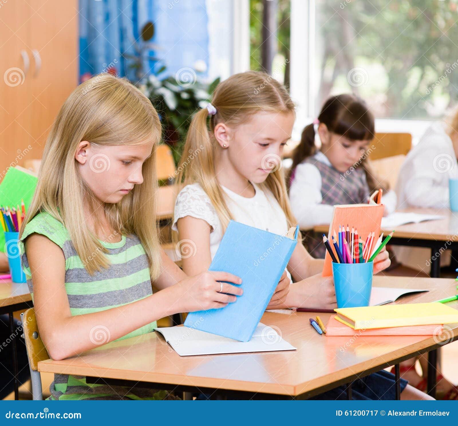 Crianças de escola primária nos livros de leitura da sala de aula