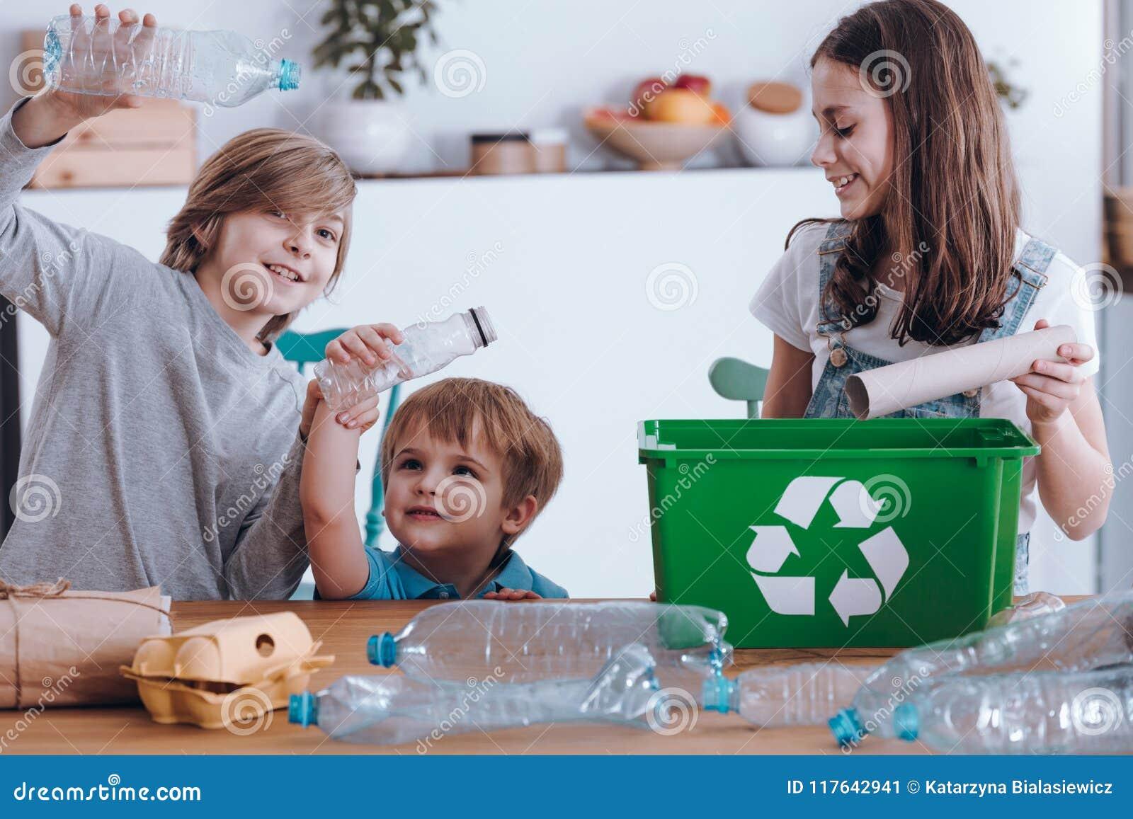 Crianças de sorriso que segregam garrafas plásticas