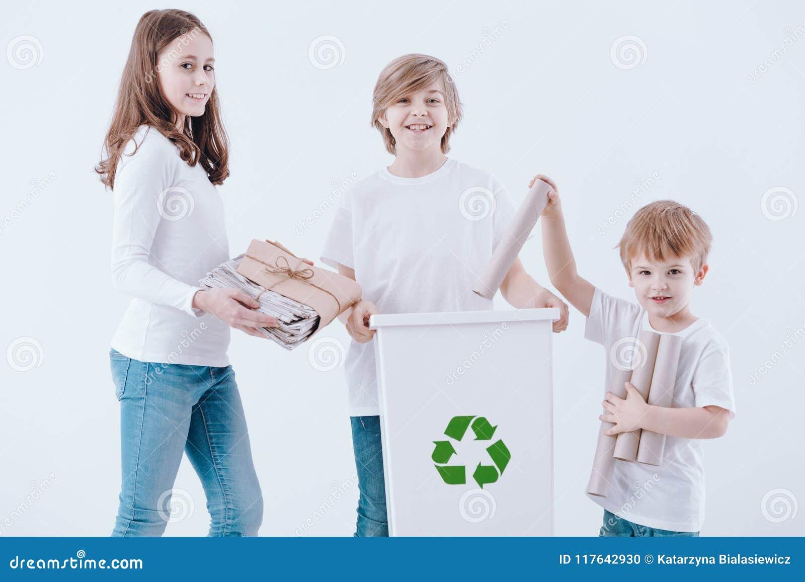 Crianças de sorriso que segregam o desperdício do papel