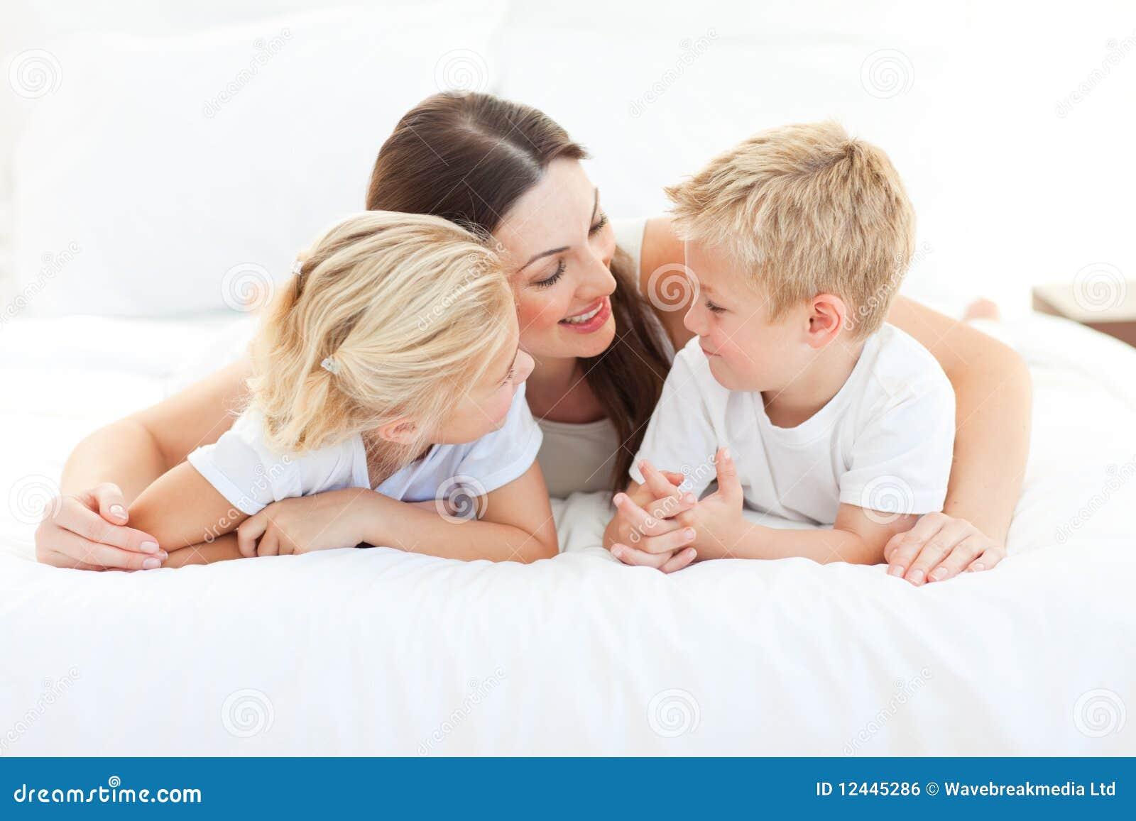 Crianças e sua mamã que discutem o encontro em uma cama
