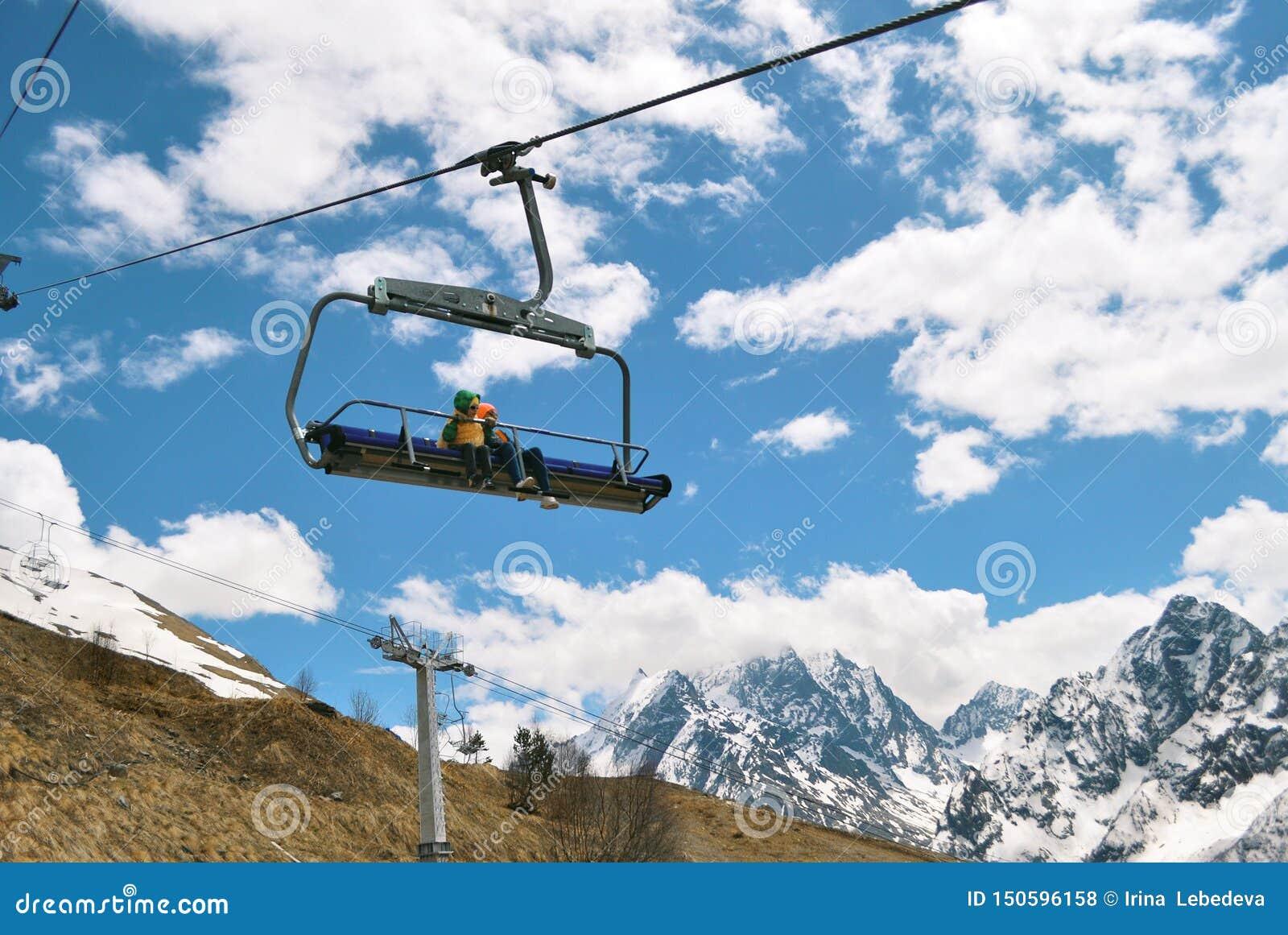 Crianças em um passeio aberto do teleférico nas montanhas nevados