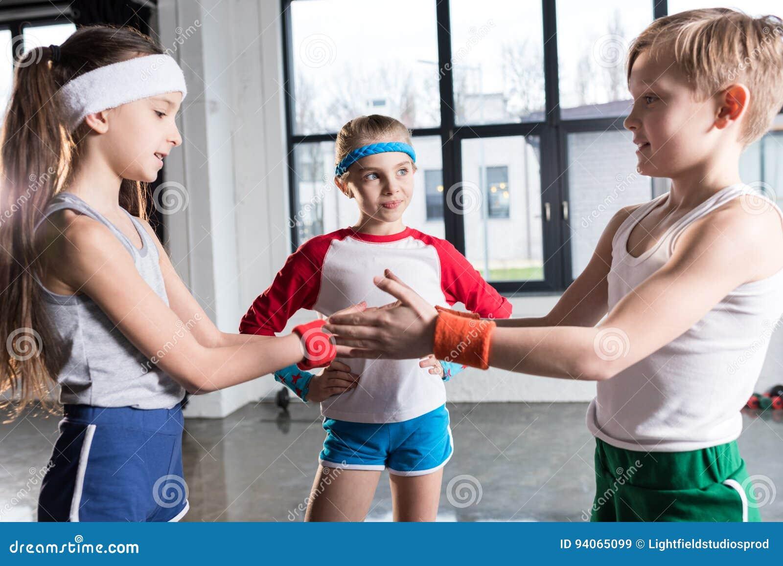 Crianças engraçadas adoráveis no sportswear que joga no estúdio da aptidão
