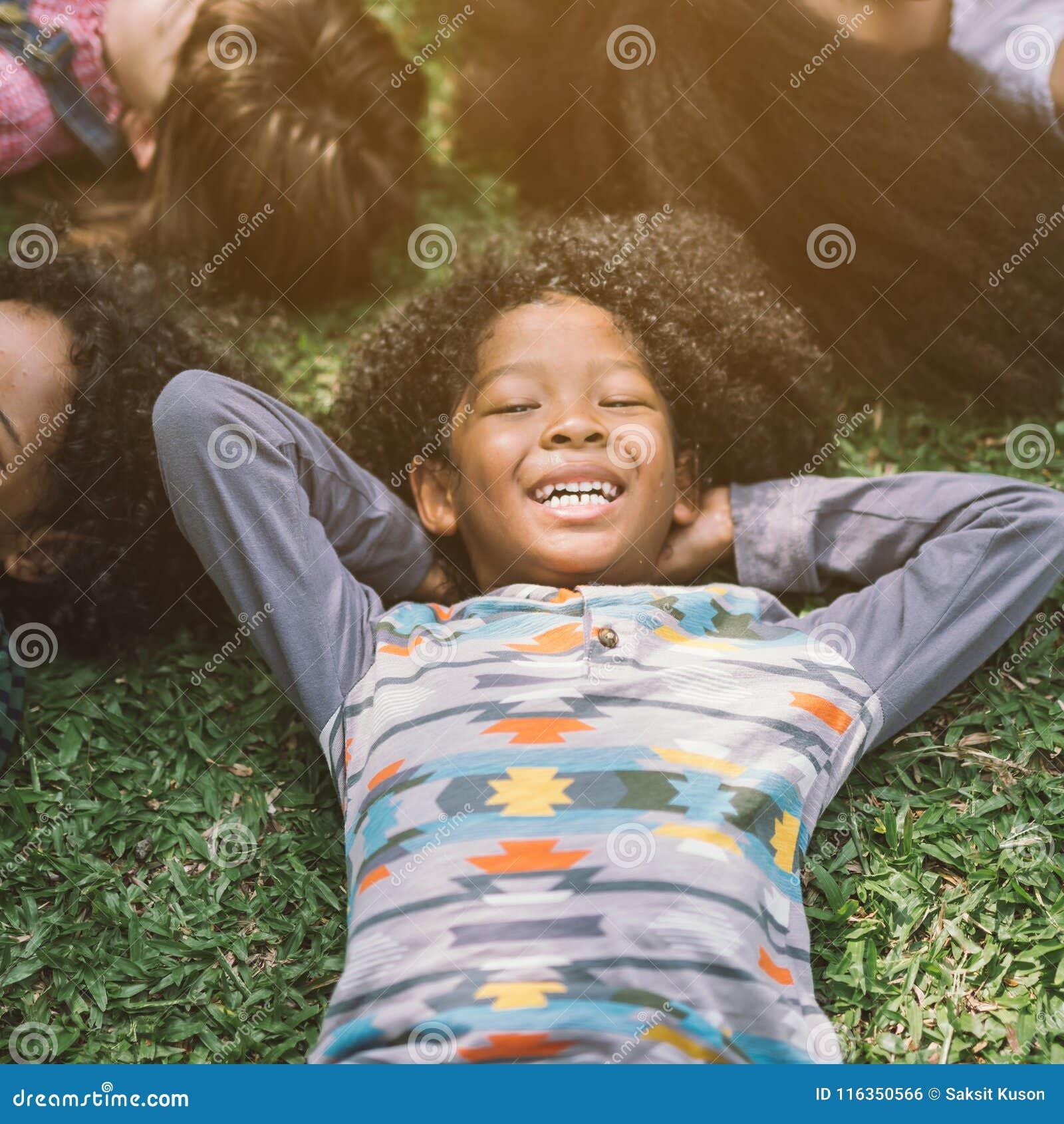Crianças felizes das crianças que colocam na grama