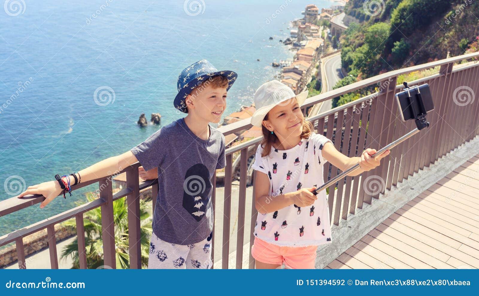 Crianças felizes dos amigos que tomam o selfie na cidade bonita de Scilla Italy, crianças de sorriso que têm o divertimento que c