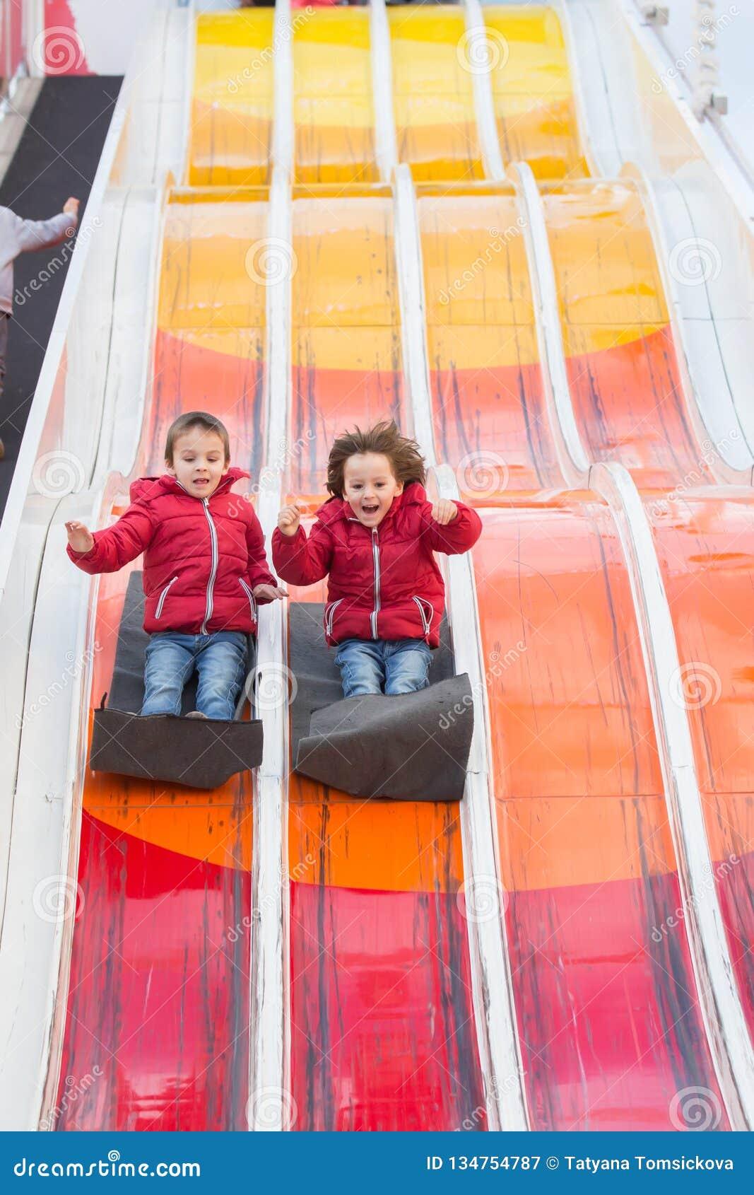 Crianças felizes, indo abaixo da corrediça enorme, feliz, apreciando