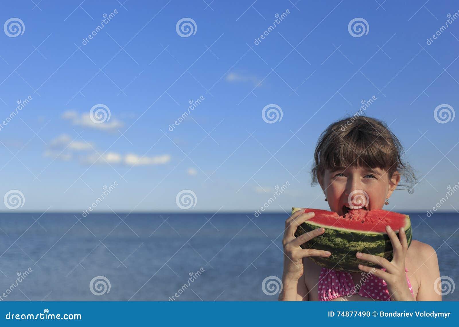Crianças felizes na praia que comem a melancia doce