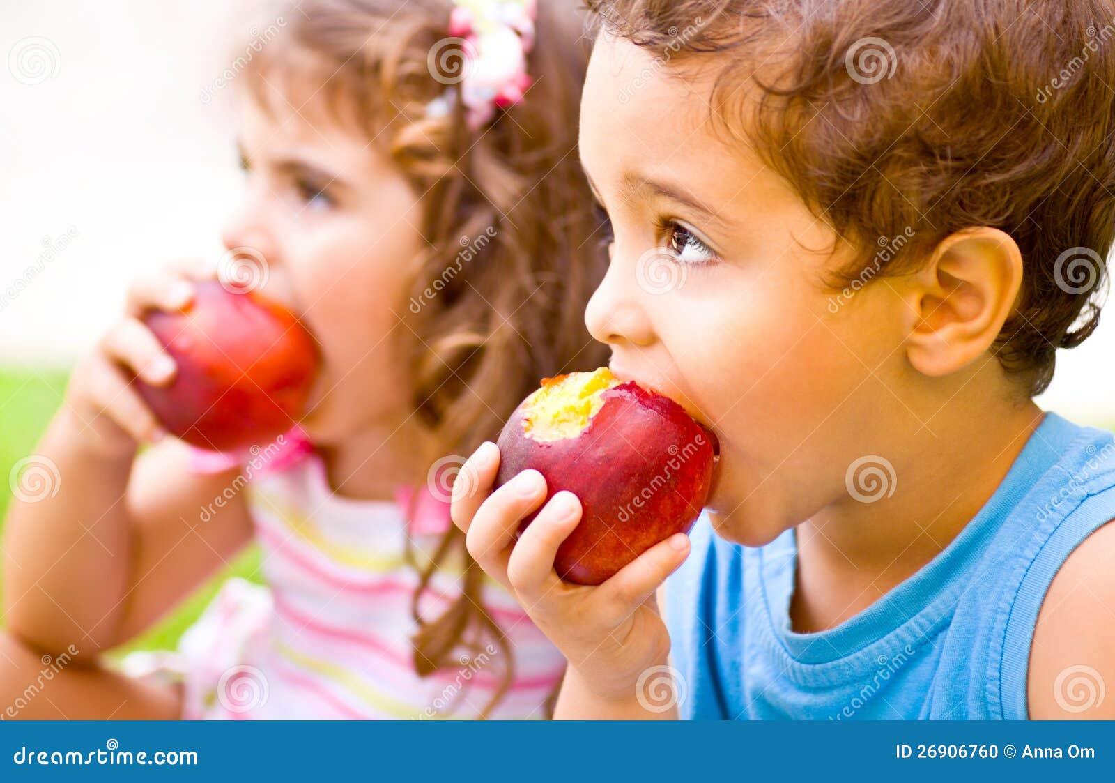 Crianças felizes que comem a maçã