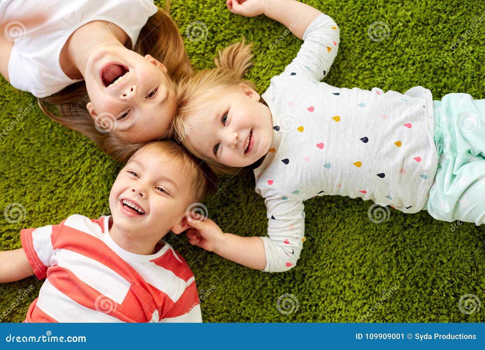 Crianças felizes que encontram-se no assoalho ou no tapete