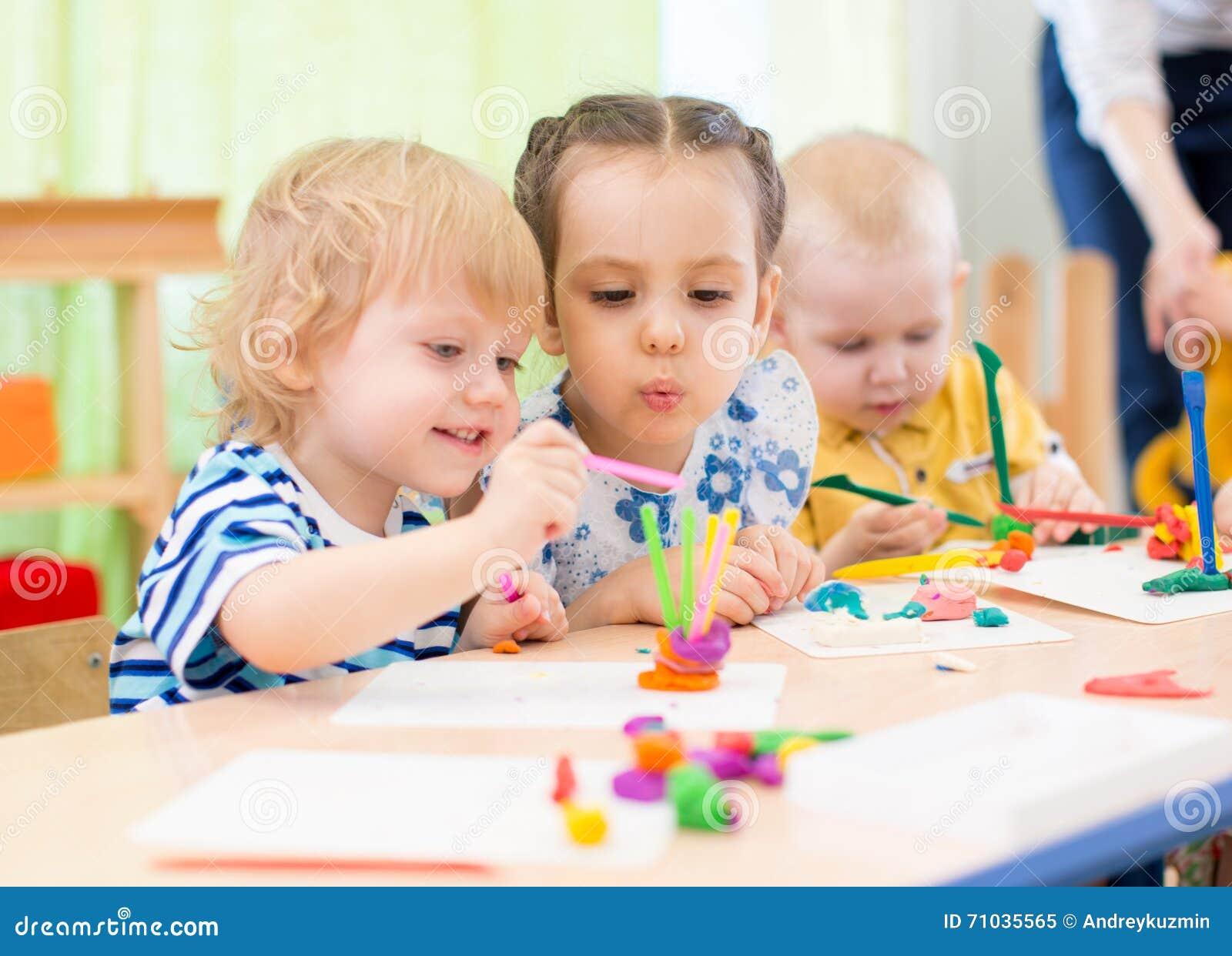 Crianças felizes que fazem artes e ofícios no centro de centro de dia