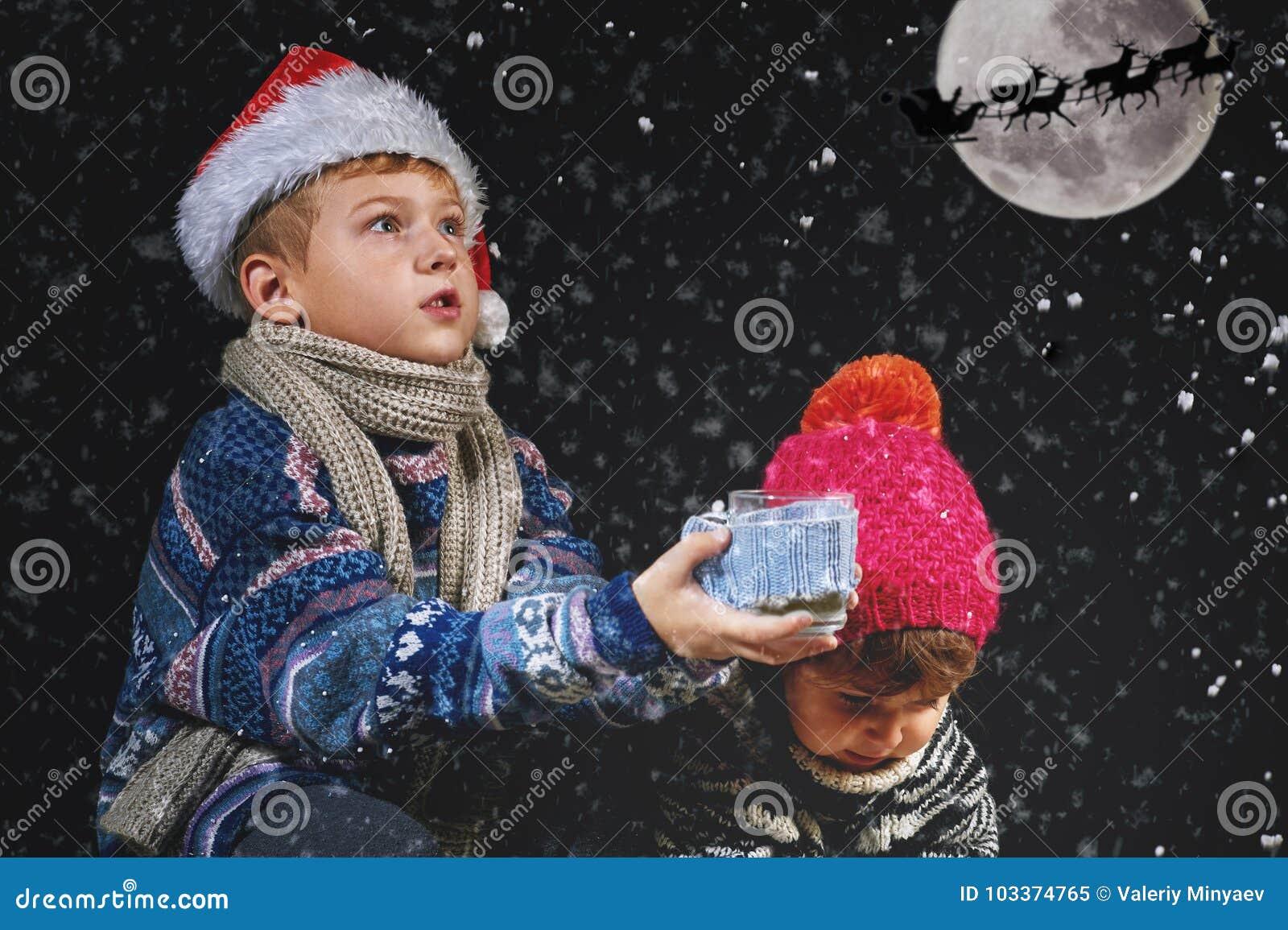 Crianças felizes que jogam com os flocos de neve na caminhada do inverno