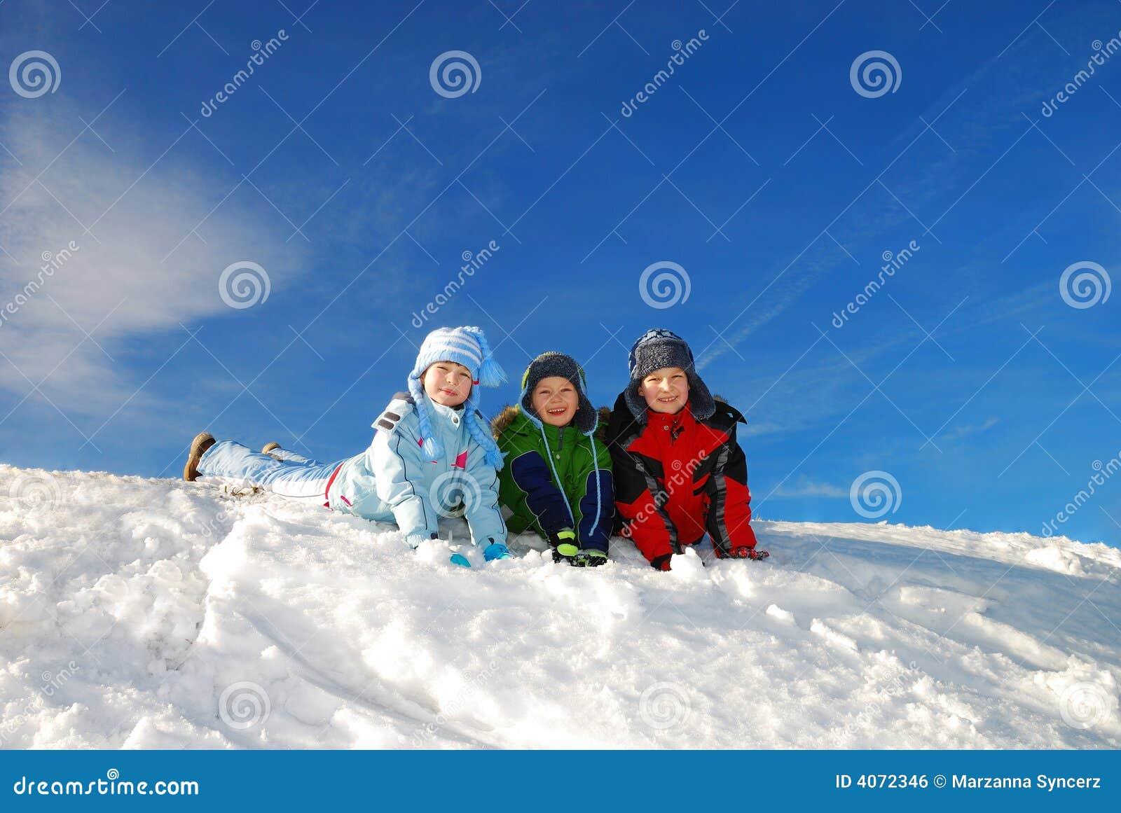 Crianças felizes que jogam na neve