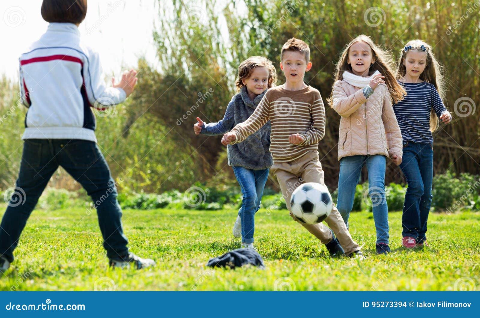 Crianças felizes que jogam o futebol fora