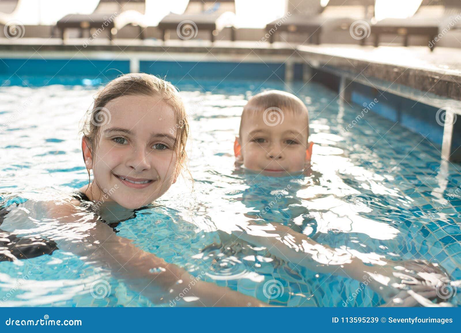 Crianças felizes que nadam na associação