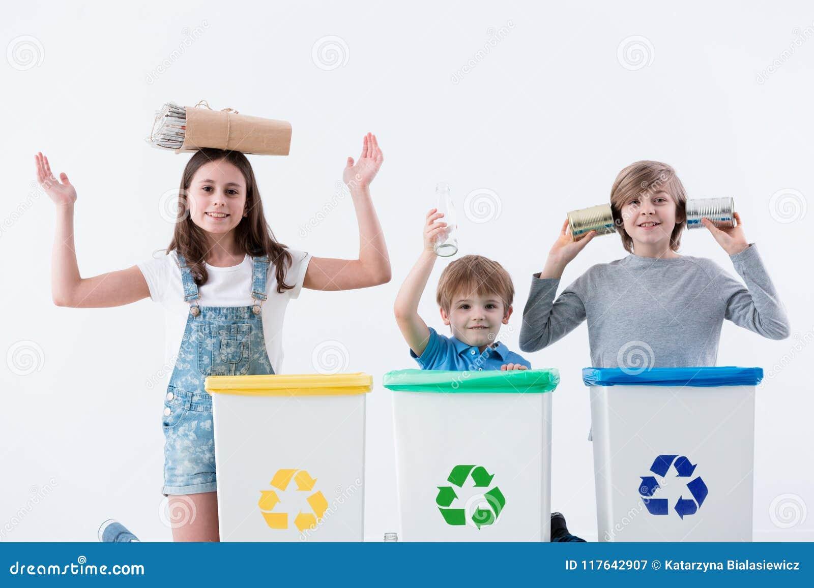Crianças felizes que segregam o desperdício do agregado familiar