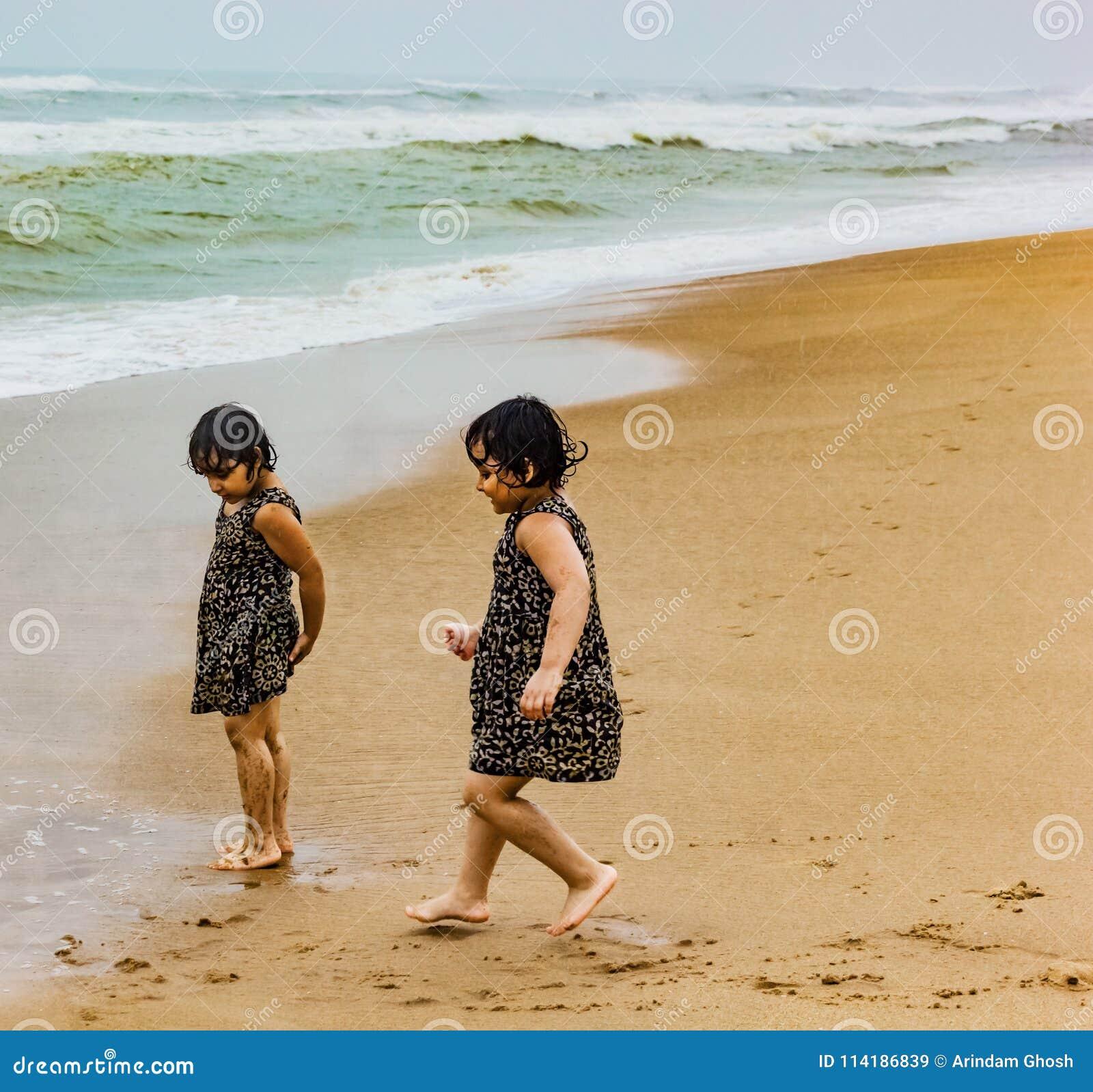 Crianças indianas das irmãs gêmeas que correm no Sandy Beach do puri no litoral que expressa a alegria