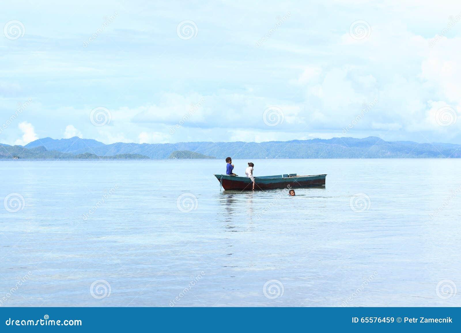 Crianças indonésias que jogam no mar