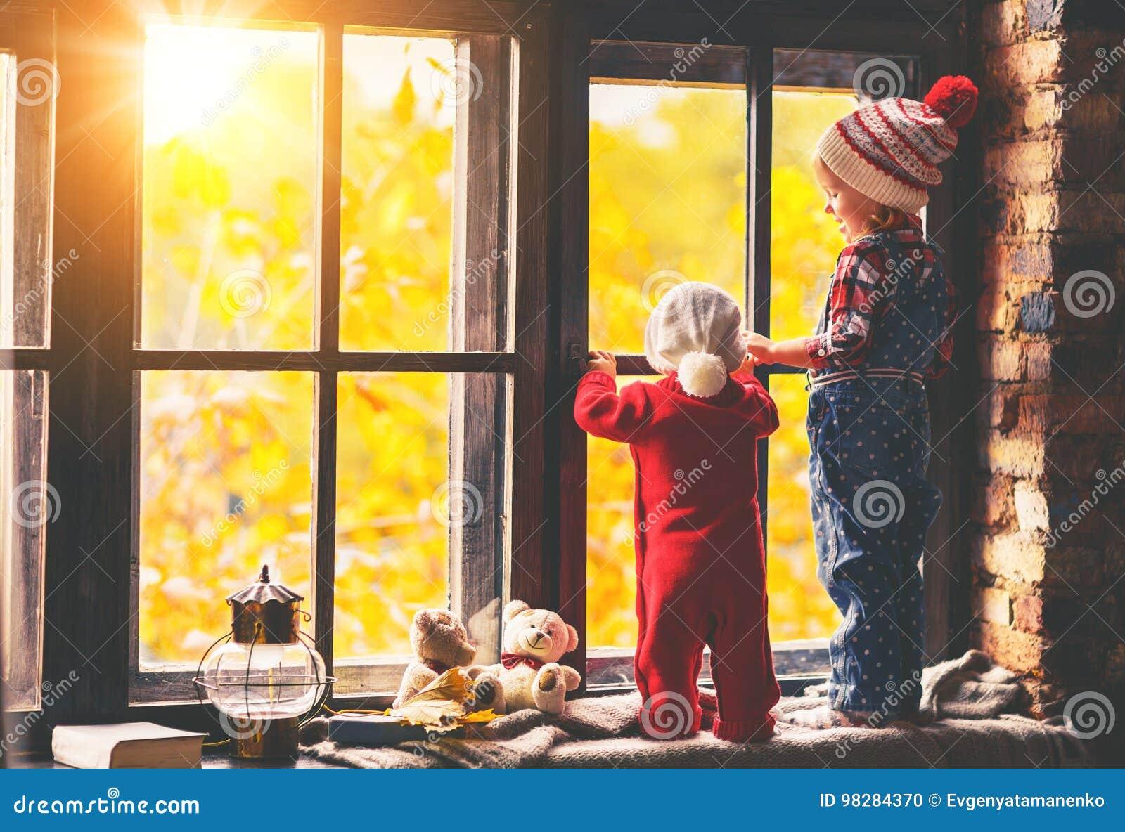 Crianças irmão e irmã que admiram a janela para o outono