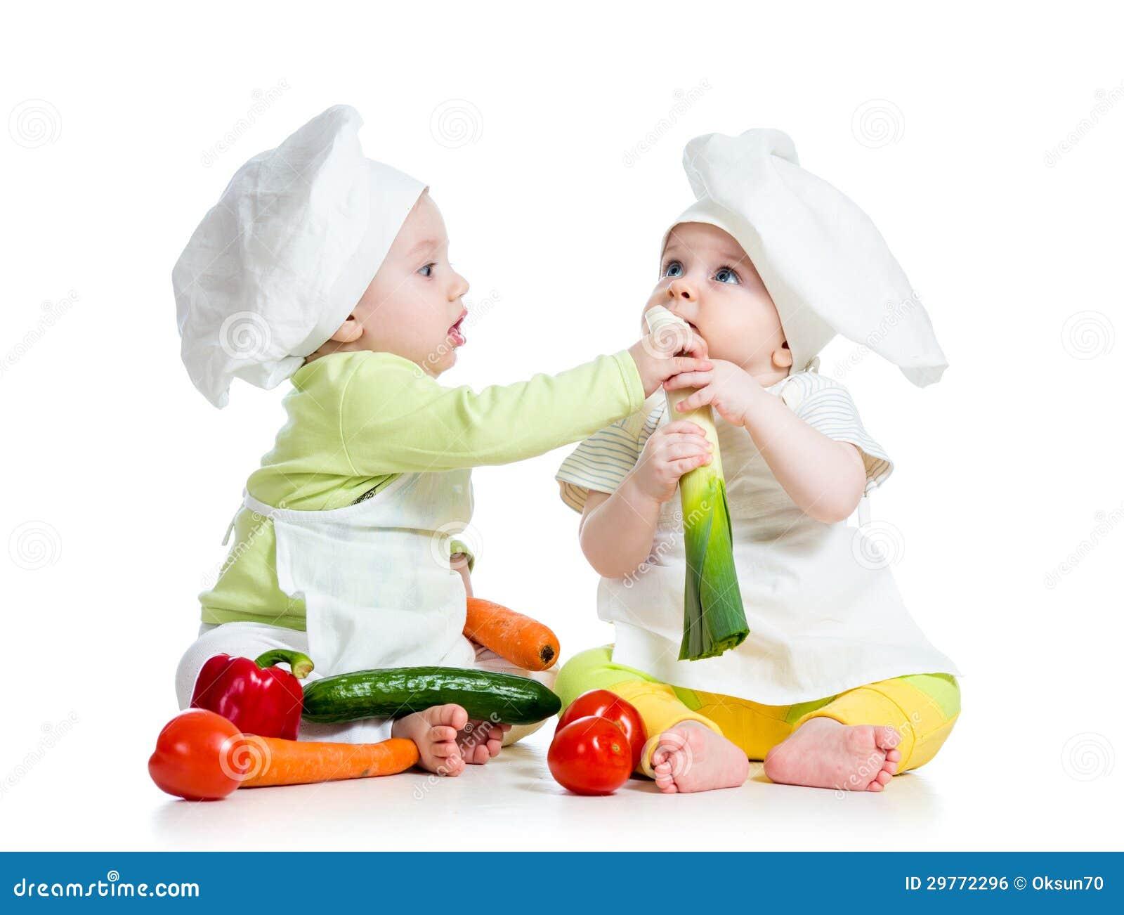 Menina do menino das crianças que come o alimento saudável