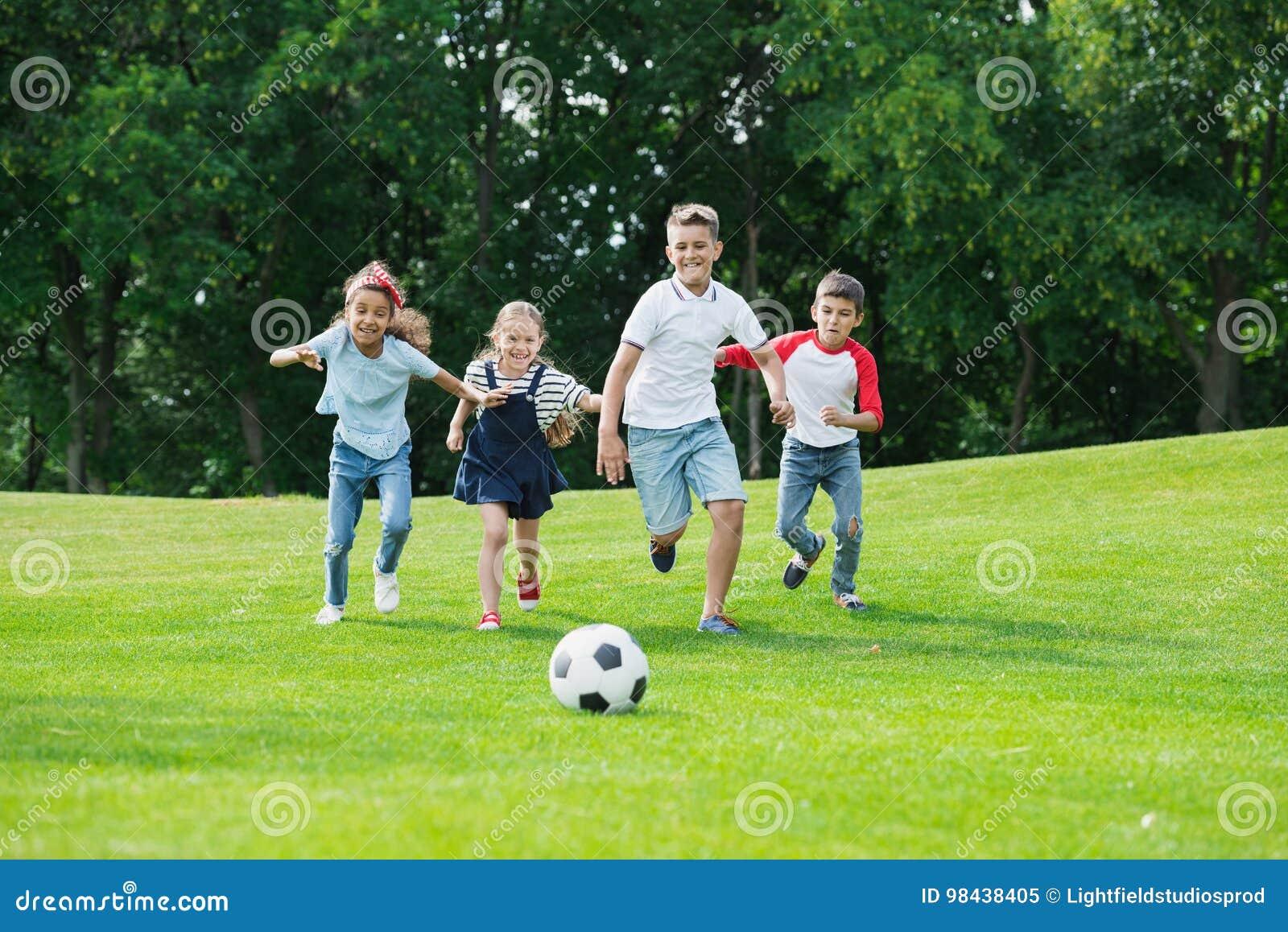 Crianças multi-étnicos felizes que jogam o futebol com a bola no parque