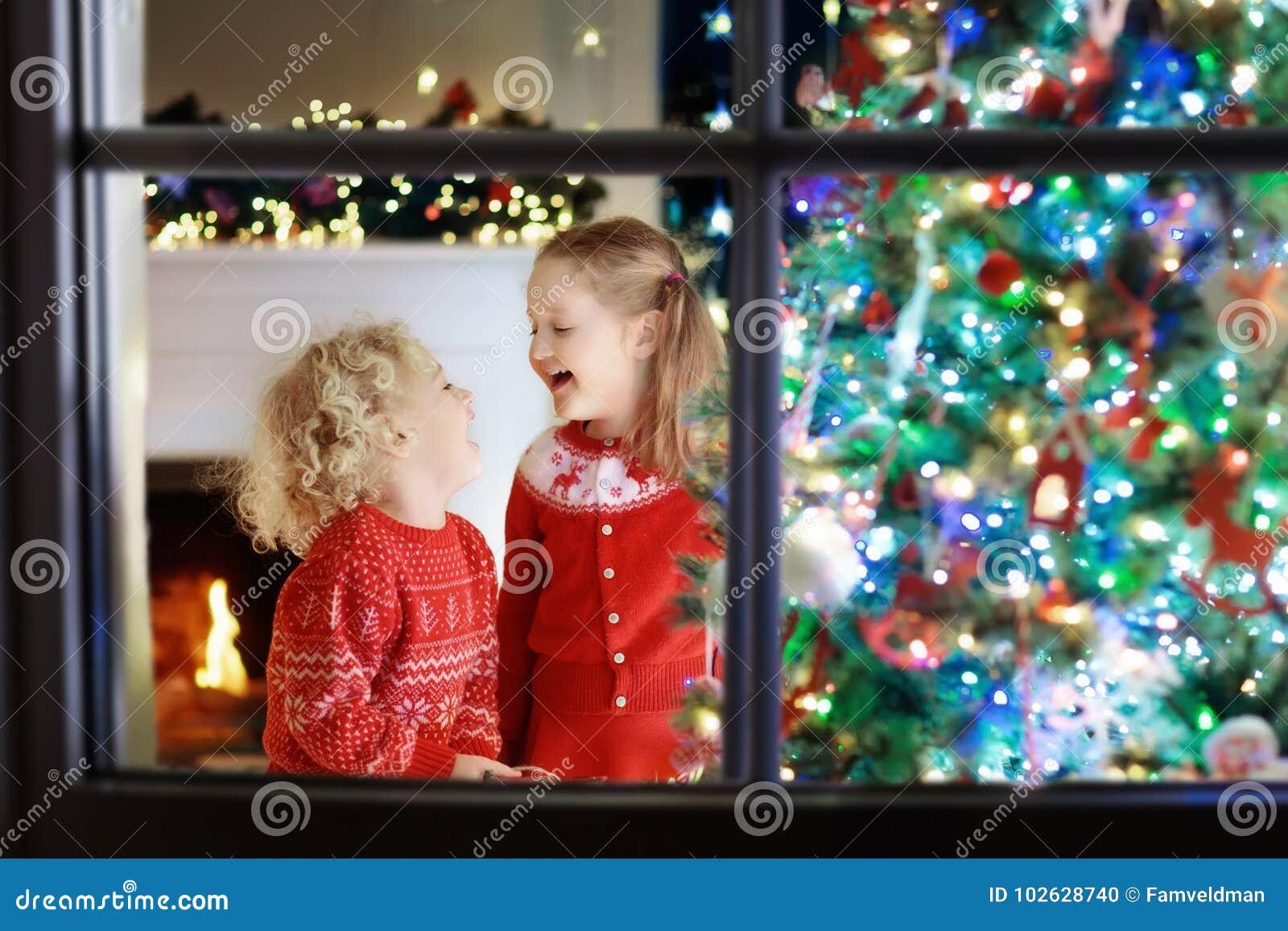 Crianças na árvore de Natal Crianças na chaminé na véspera do Xmas