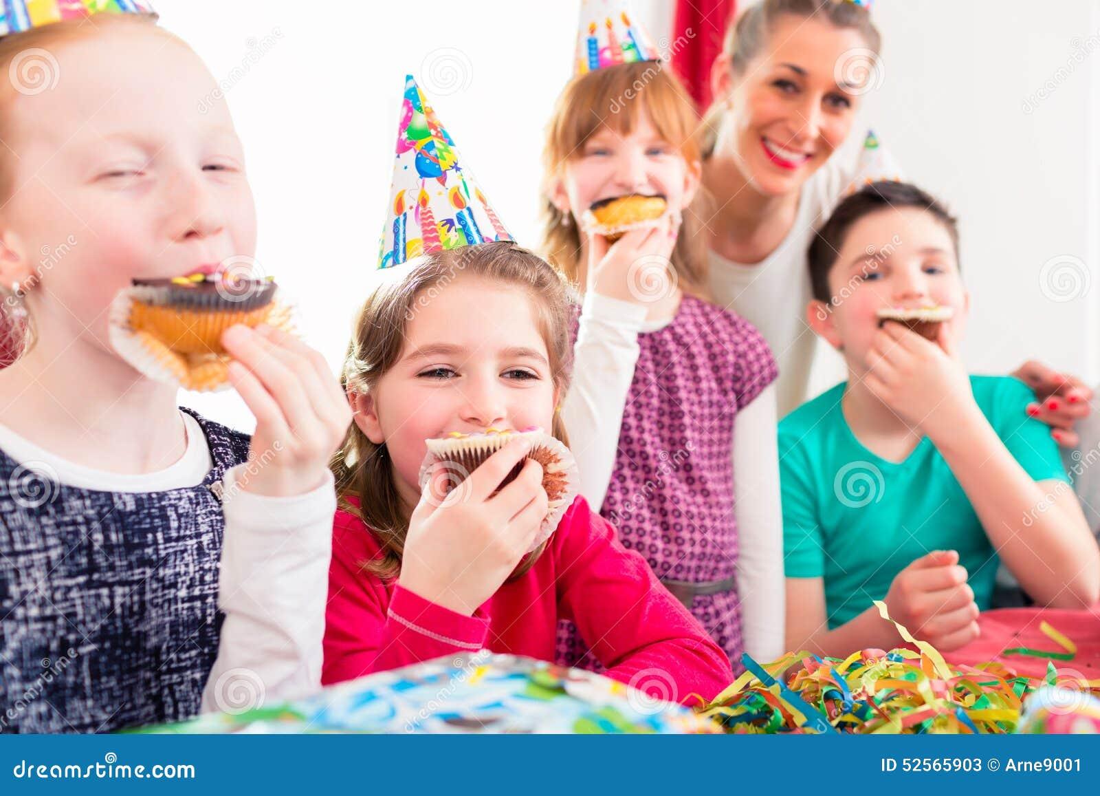 Crianças na festa de anos com queques e bolo