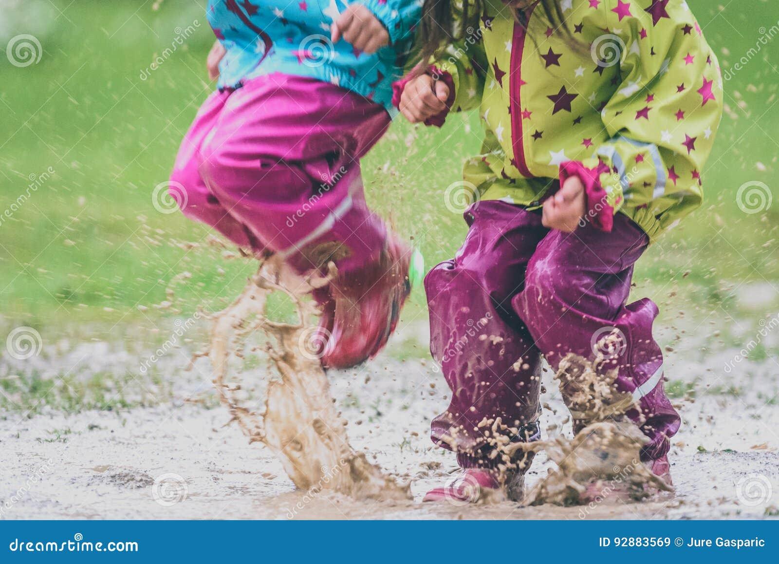 Crianças nas botas de borracha e na roupa da chuva que saltam na poça
