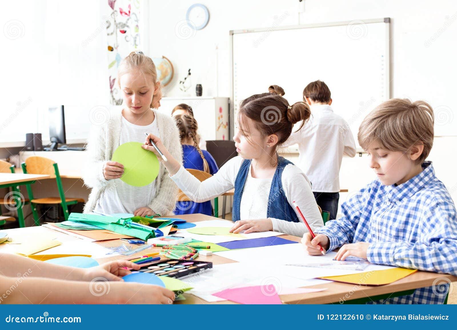 Crianças nas imagens da pintura da sala de aula durante classes de arte