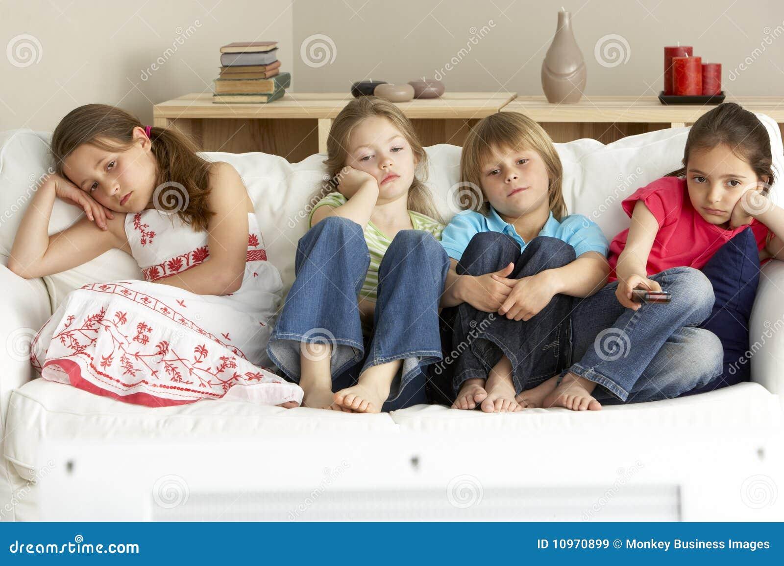 Crianças novas que prestam atenção à televisão em casa