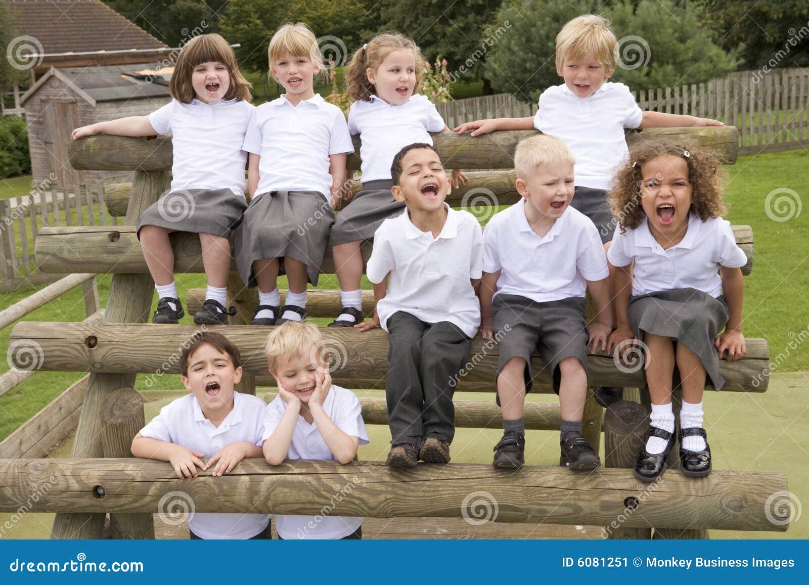 Crianças novas que sentam-se em bancos e em gritar