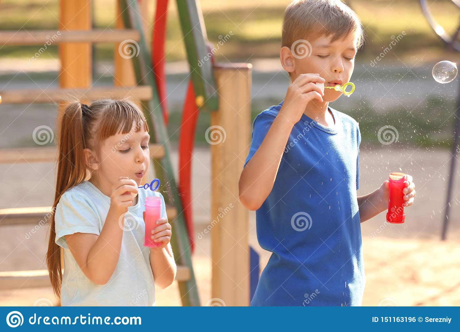 Crianças pequenas bonitos que fundem bolhas de sabão fora
