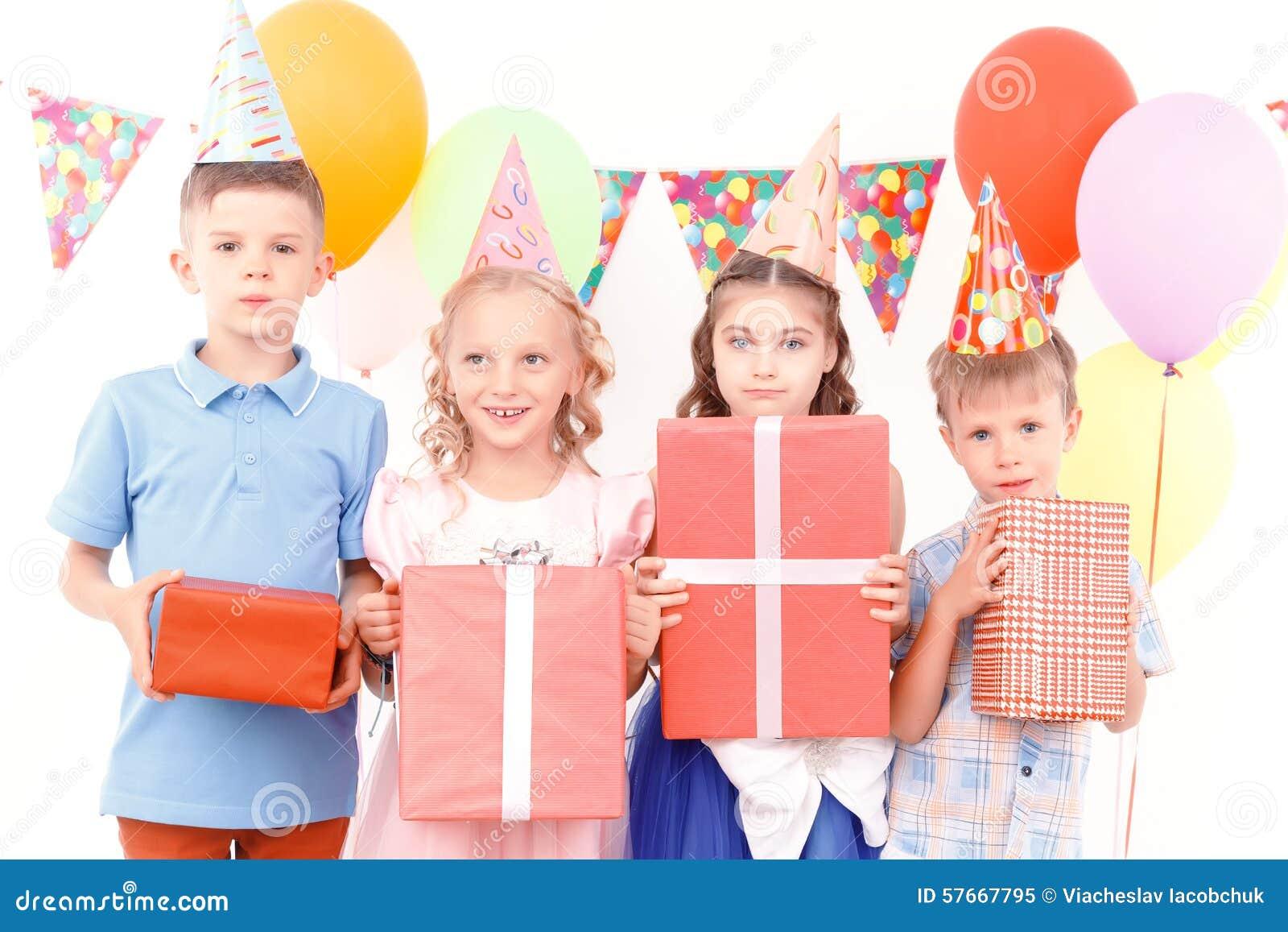 Crianças pequenas que levantam com presentes de aniversário