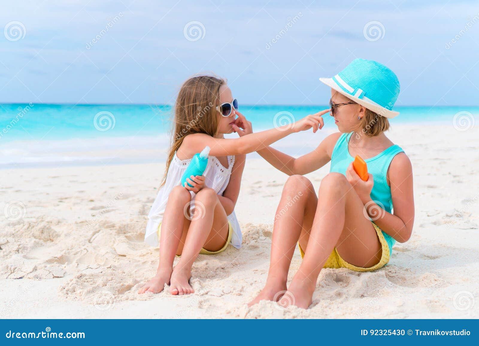 Crianças que aplicam o creme do sol entre si na praia O conceito da proteção da radiação ultravioleta