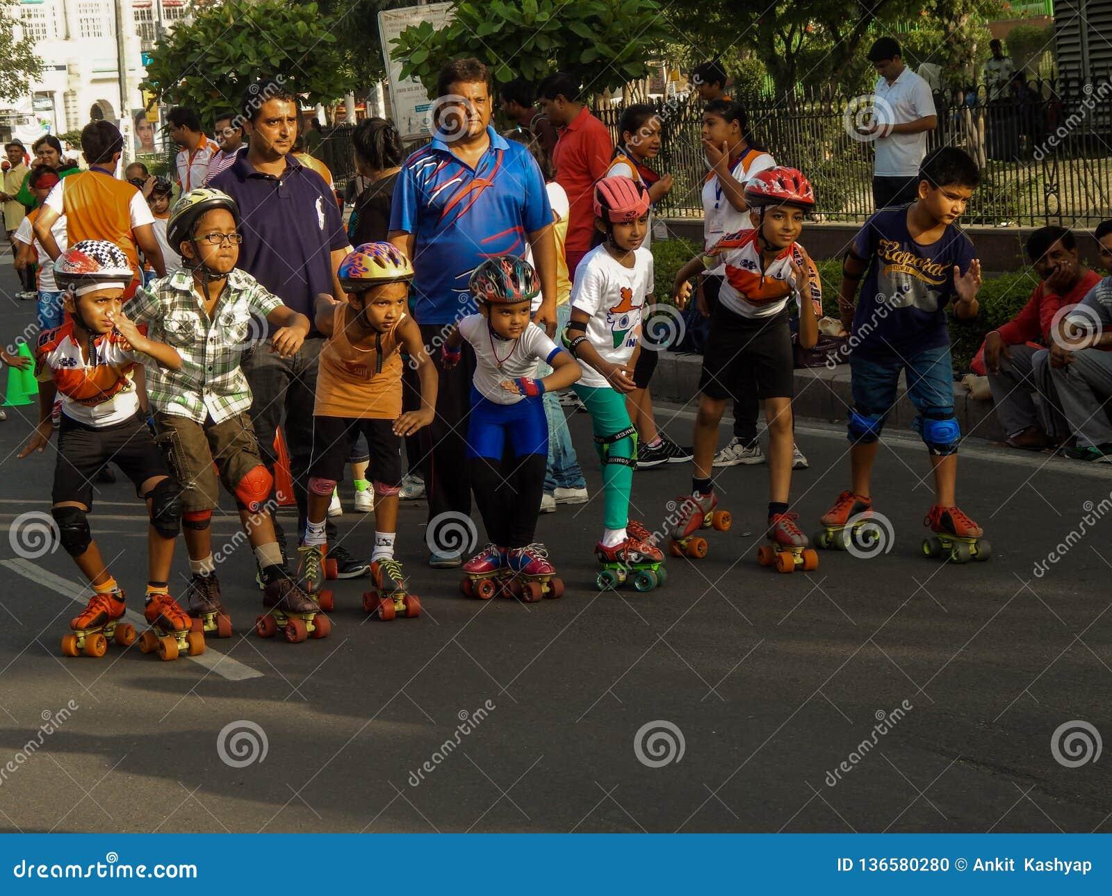 Crianças que apreciam a patinagem com seus pais