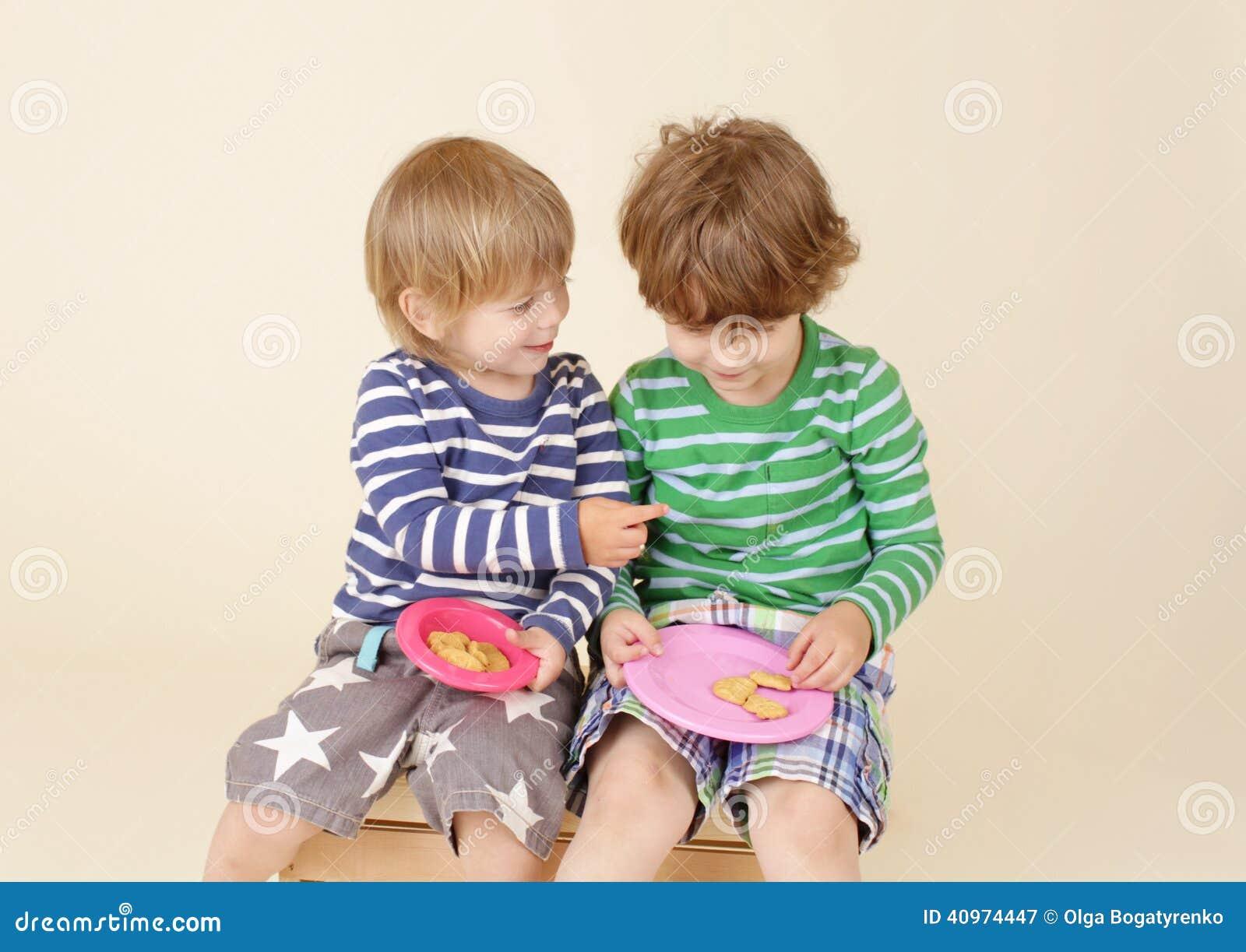 Crianças que compartilham de um petisco, alimento, a forma das crianças
