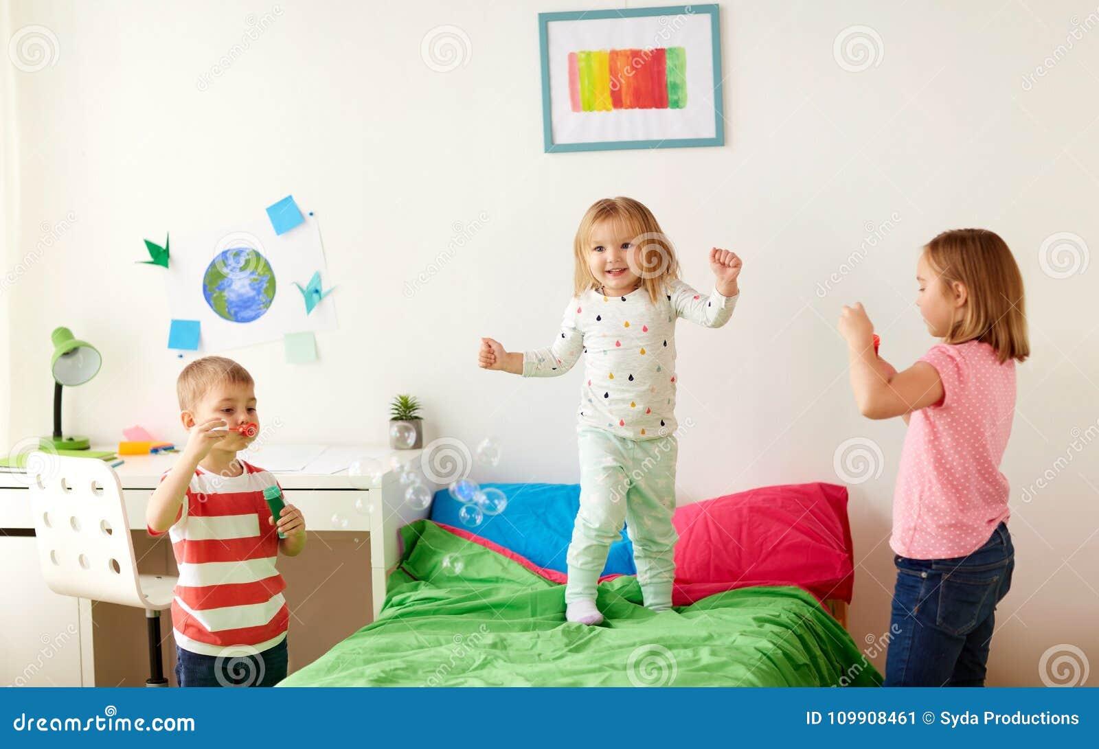 Crianças que fundem bolhas de sabão e que jogam em casa