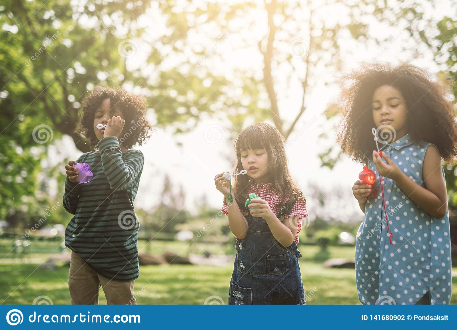 Crianças que jogam bolhas de sopro junto no campo