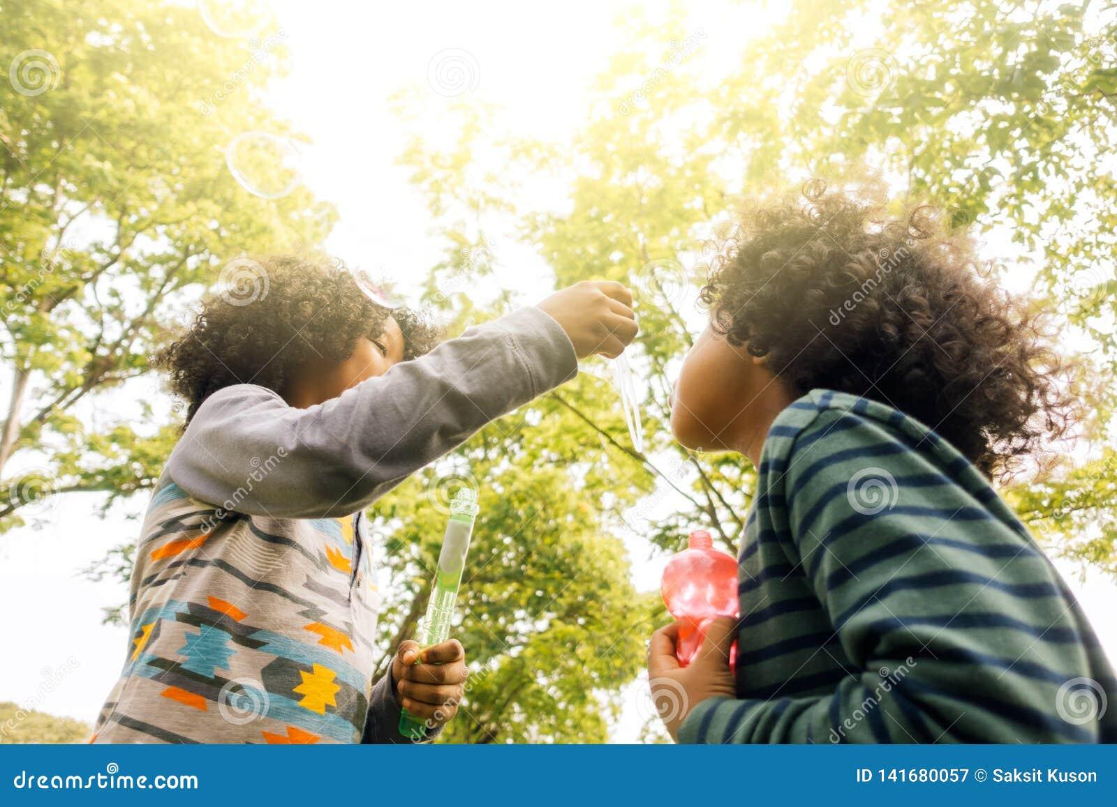 Crianças que jogam com amigos Crianças que jogam bolhas de sopro