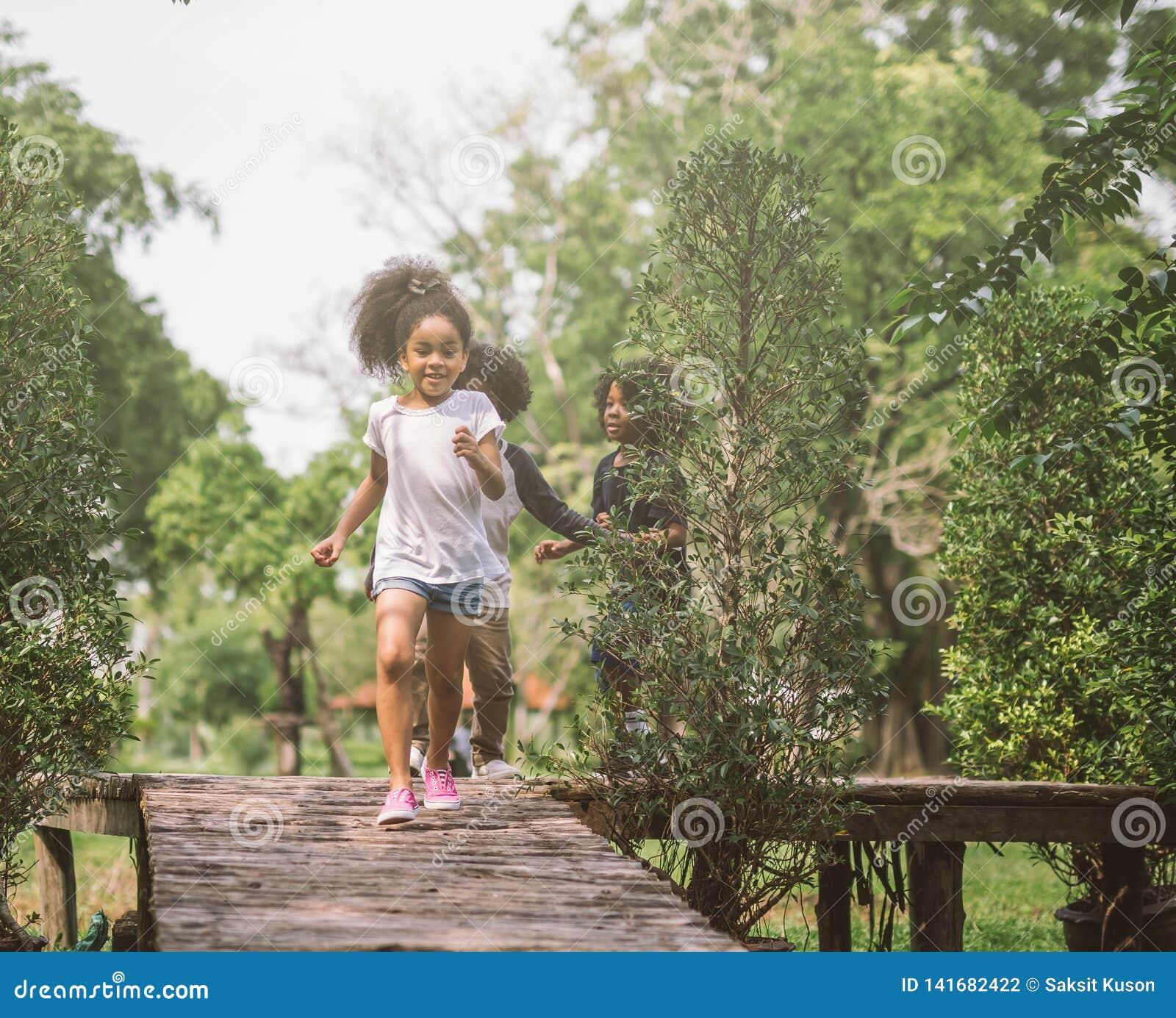 Crianças que jogam com amigos Crianças que correm no parque