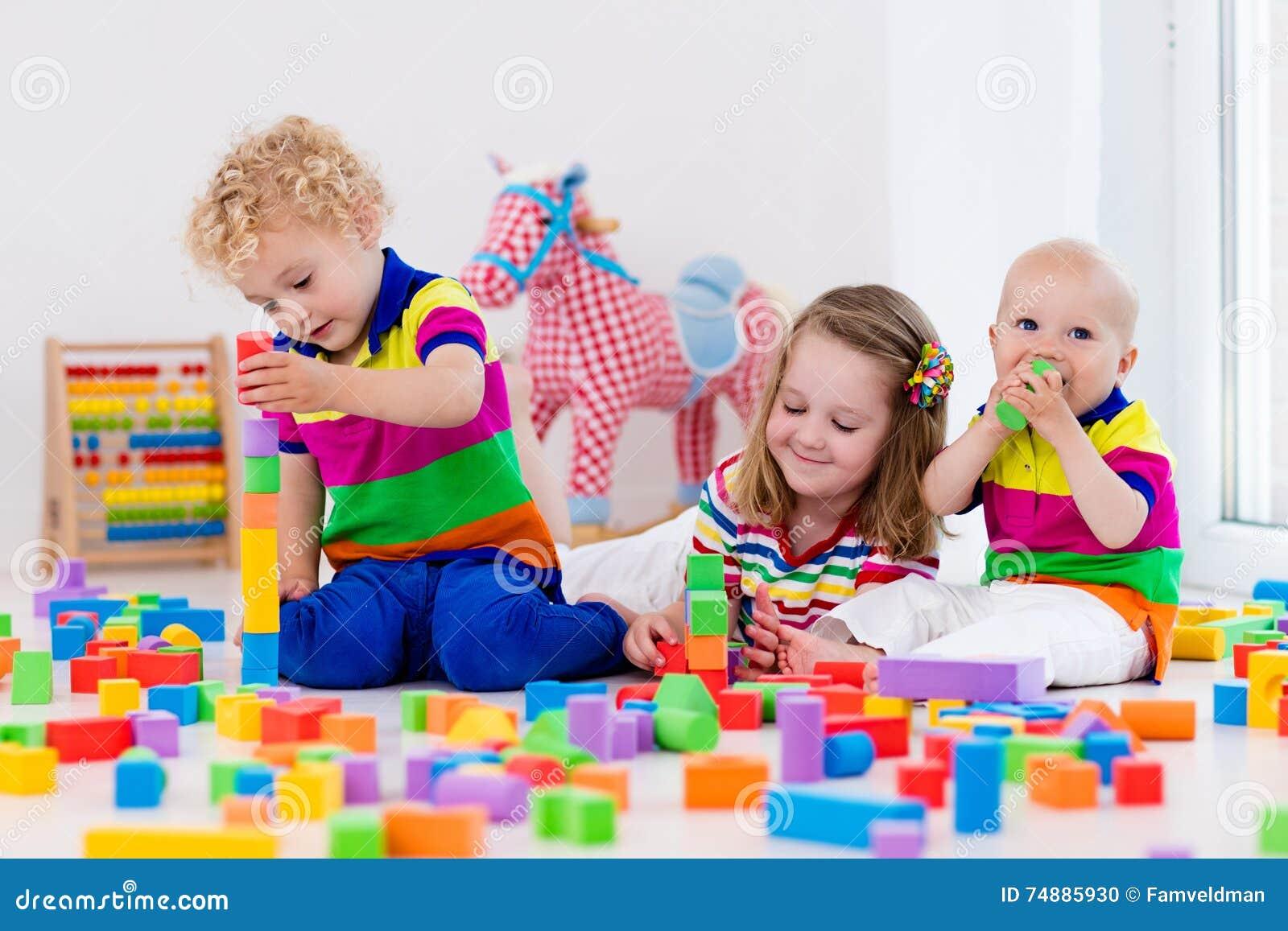 Crianças que jogam com blocos coloridos do brinquedo