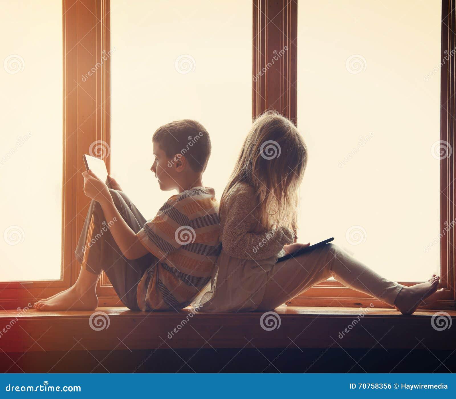 Crianças que jogam em tabuletas da tecnologia em casa