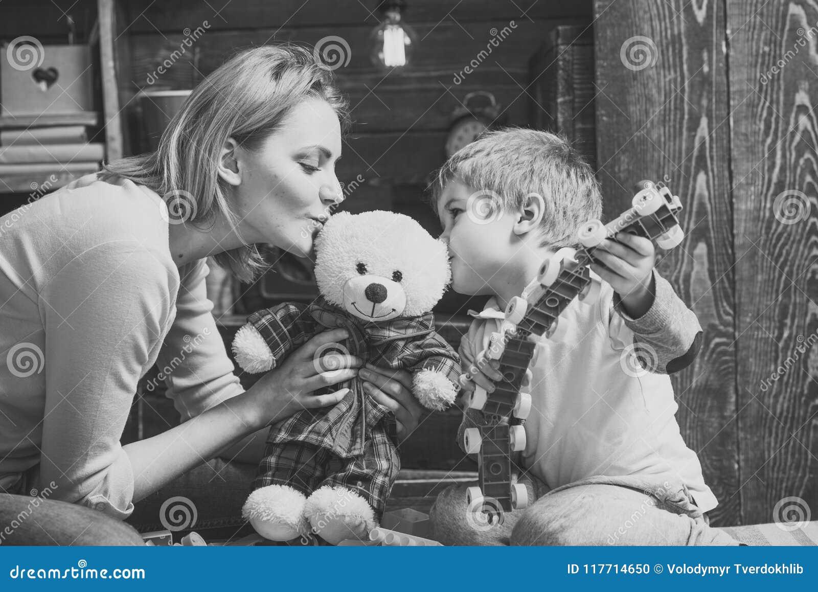 Crianças que jogam - jogo feliz Conceito da bondade e da educação A mãe ensina o filho ser amável e amigável Berçário de madeira
