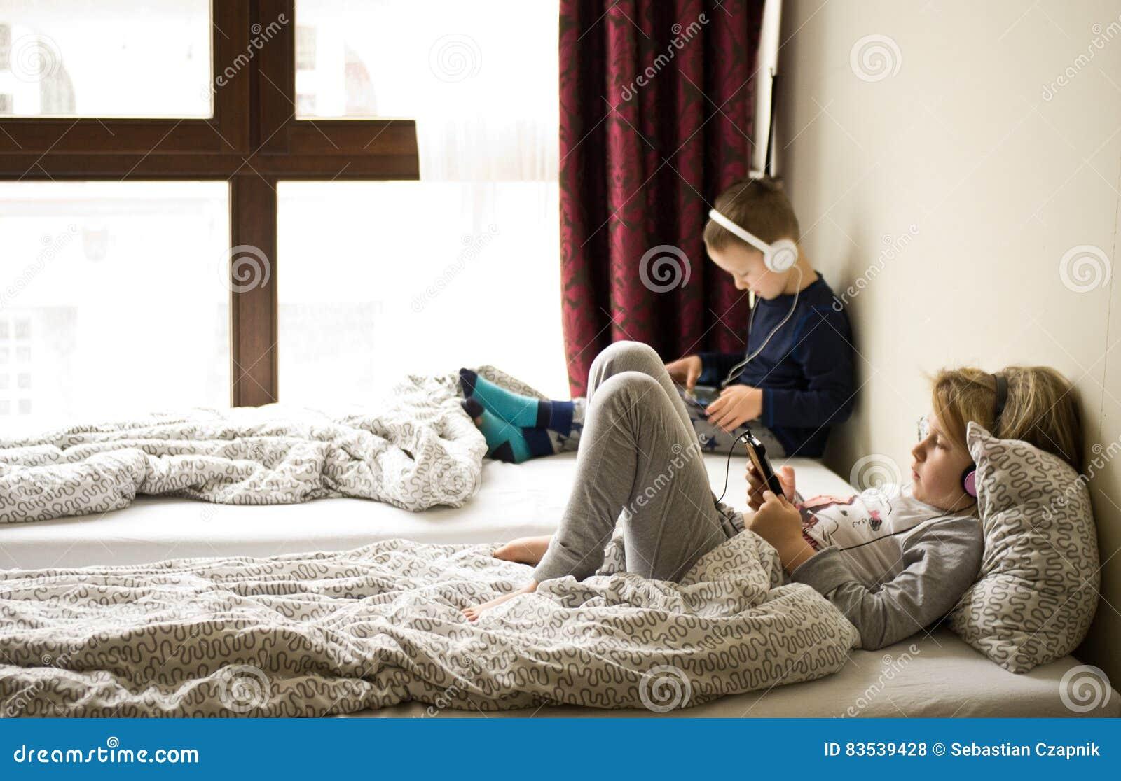 Crianças que jogam na cama com seus tabuletas e telefones
