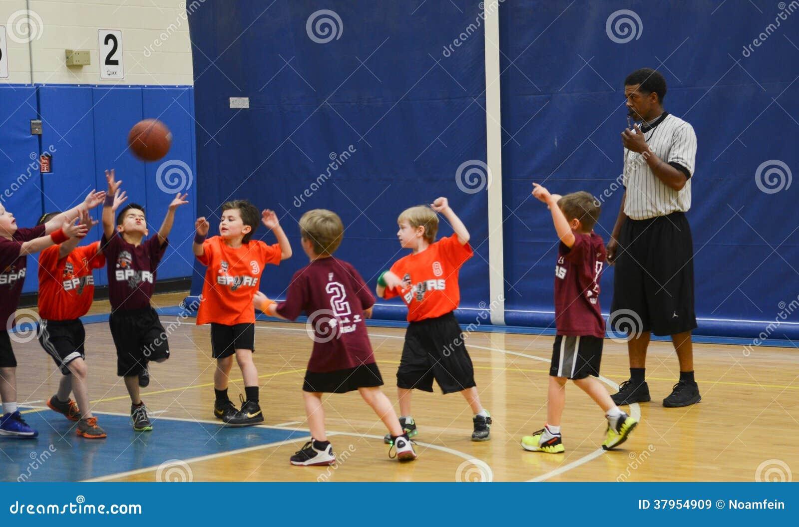 Crianças que jogam o fósforo de basquetebol