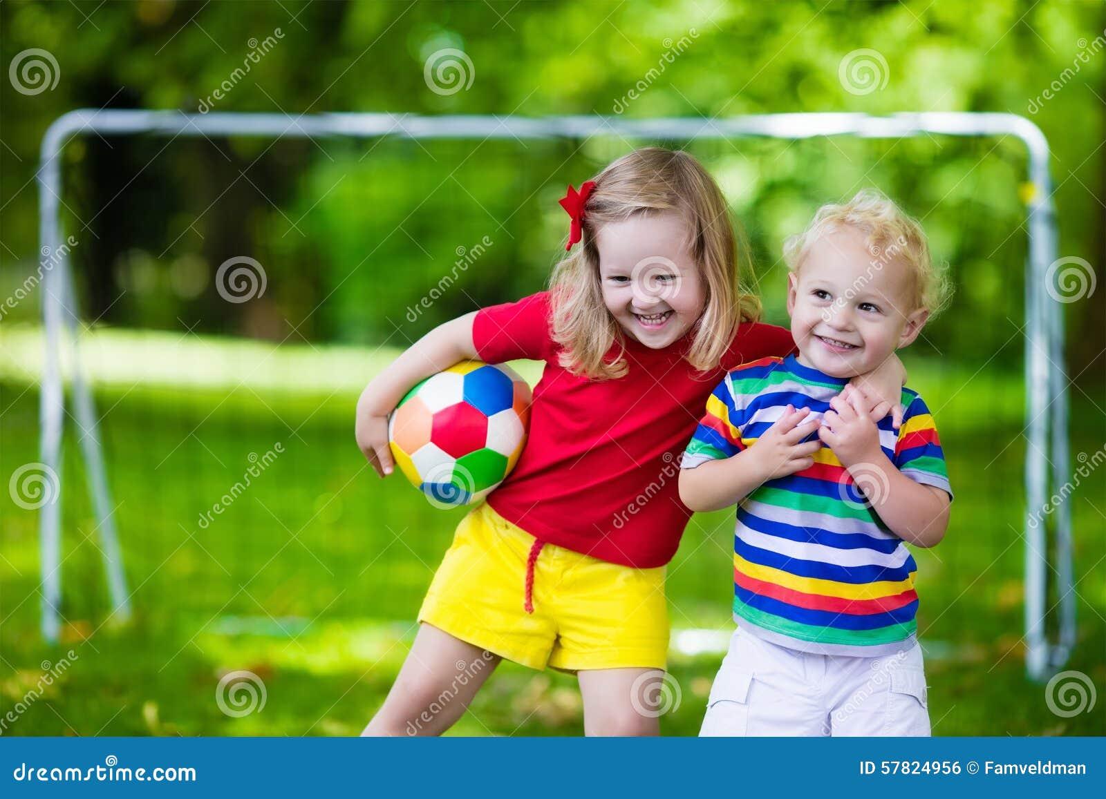 Crianças que jogam o futebol em um parque