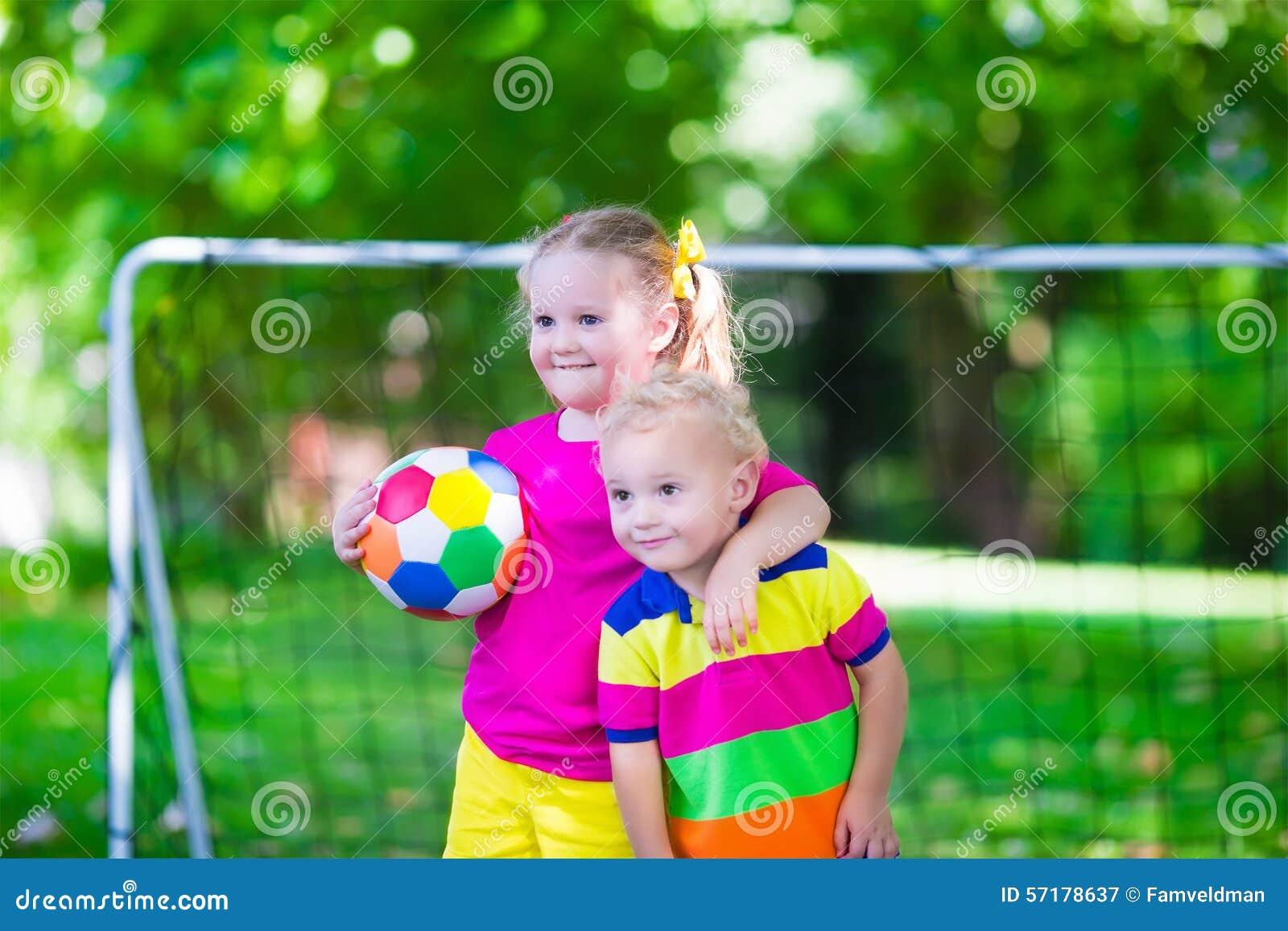 Crianças que jogam o futebol na jarda de escola