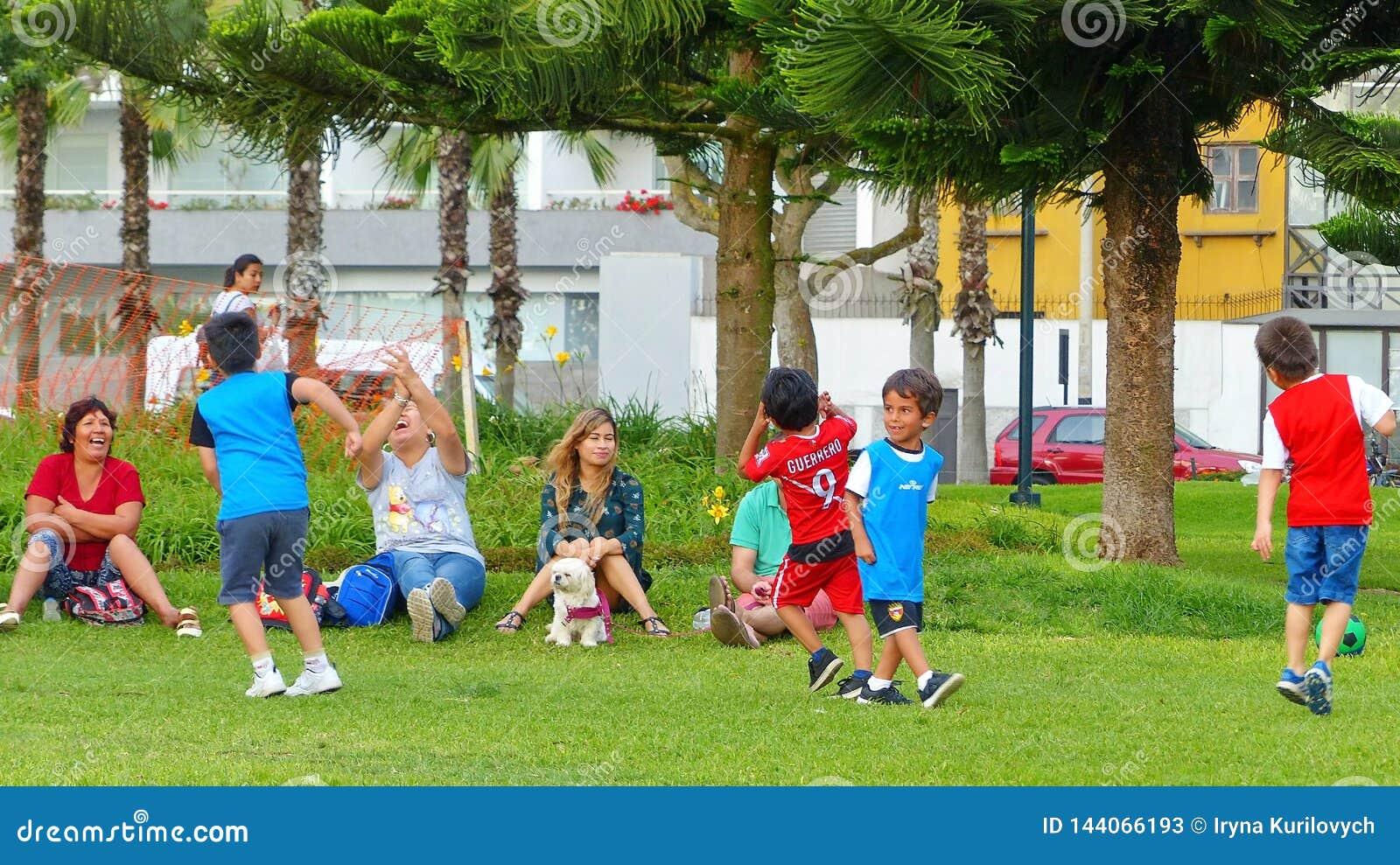 Crianças que jogam o futebol no parque de Miraflores