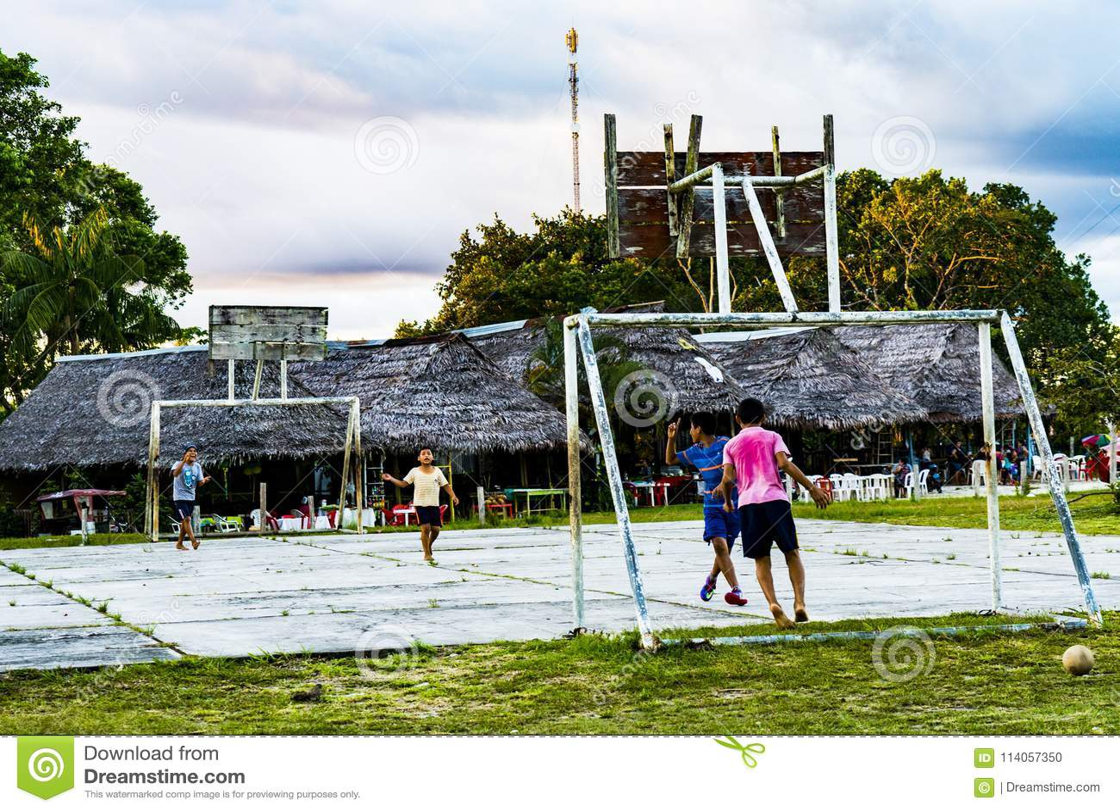 Crianças que jogam o futebol perto da floresta úmida das Amazonas de Iquitos
