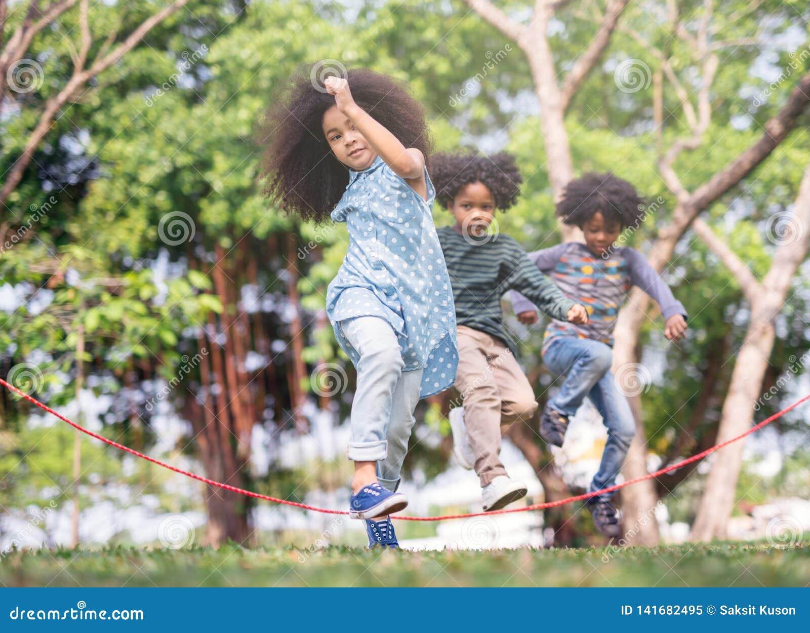 Crianças que jogam o salto sobre a corda no parque no dia de verão ensolarado